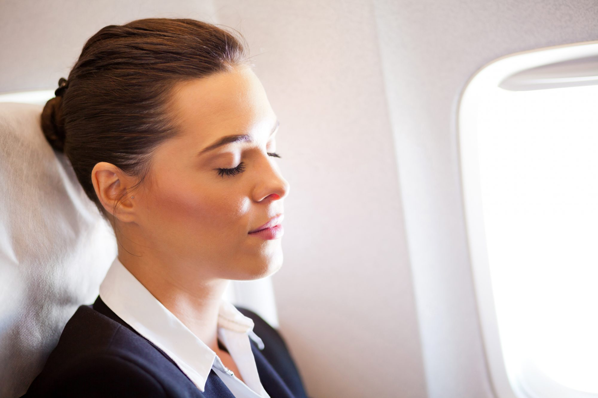 young businesswoman resting on airplane
