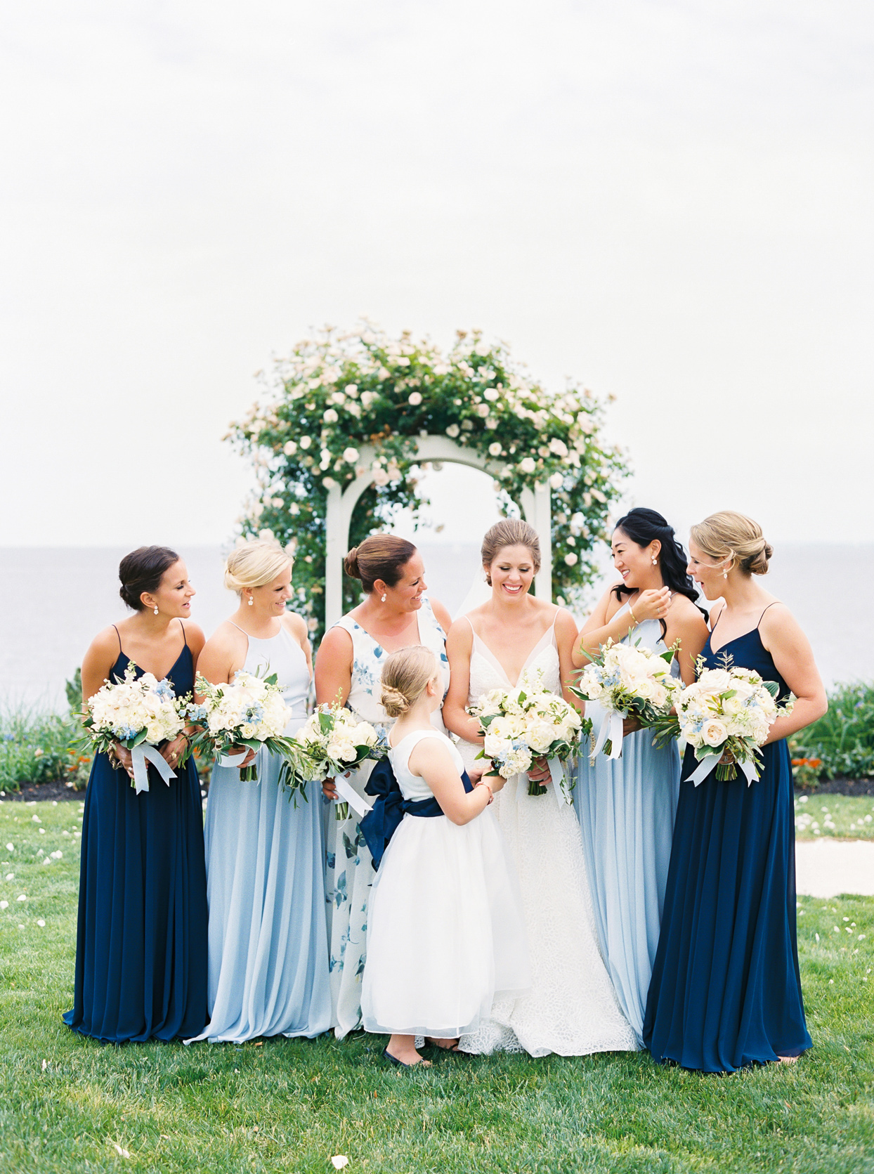 bride surrounded by bridesmaids wearing dark and light blue dresses