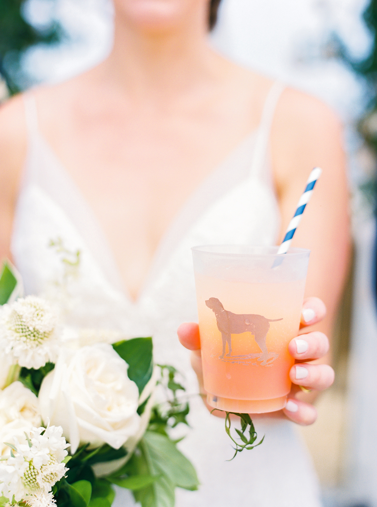 bride holding cocktail glass with dog silhouette