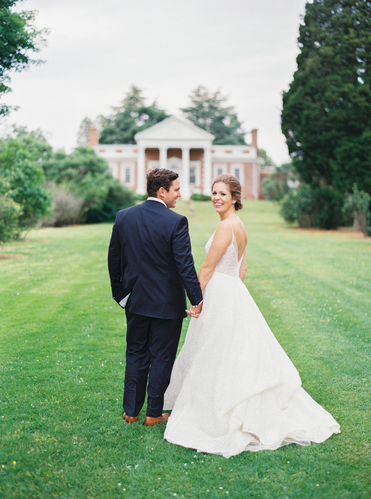 bride and groom smiling holding hands outside on green lawn