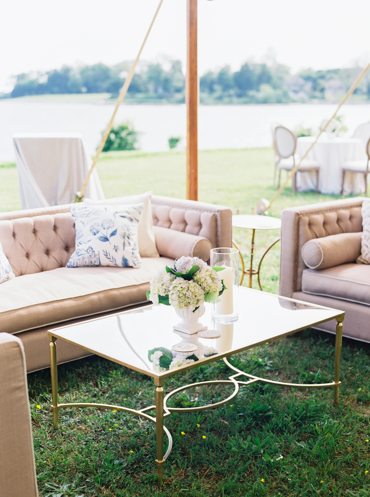beige couches and gold framed glass table top accent tables wedding lounge