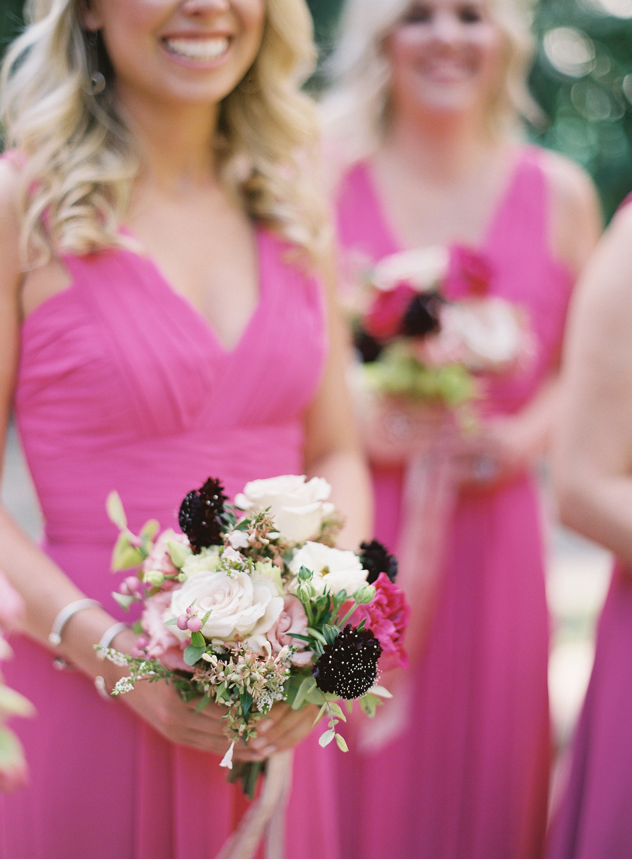 bridesmaids in bright pink dresses holding multi colored floral bouquets