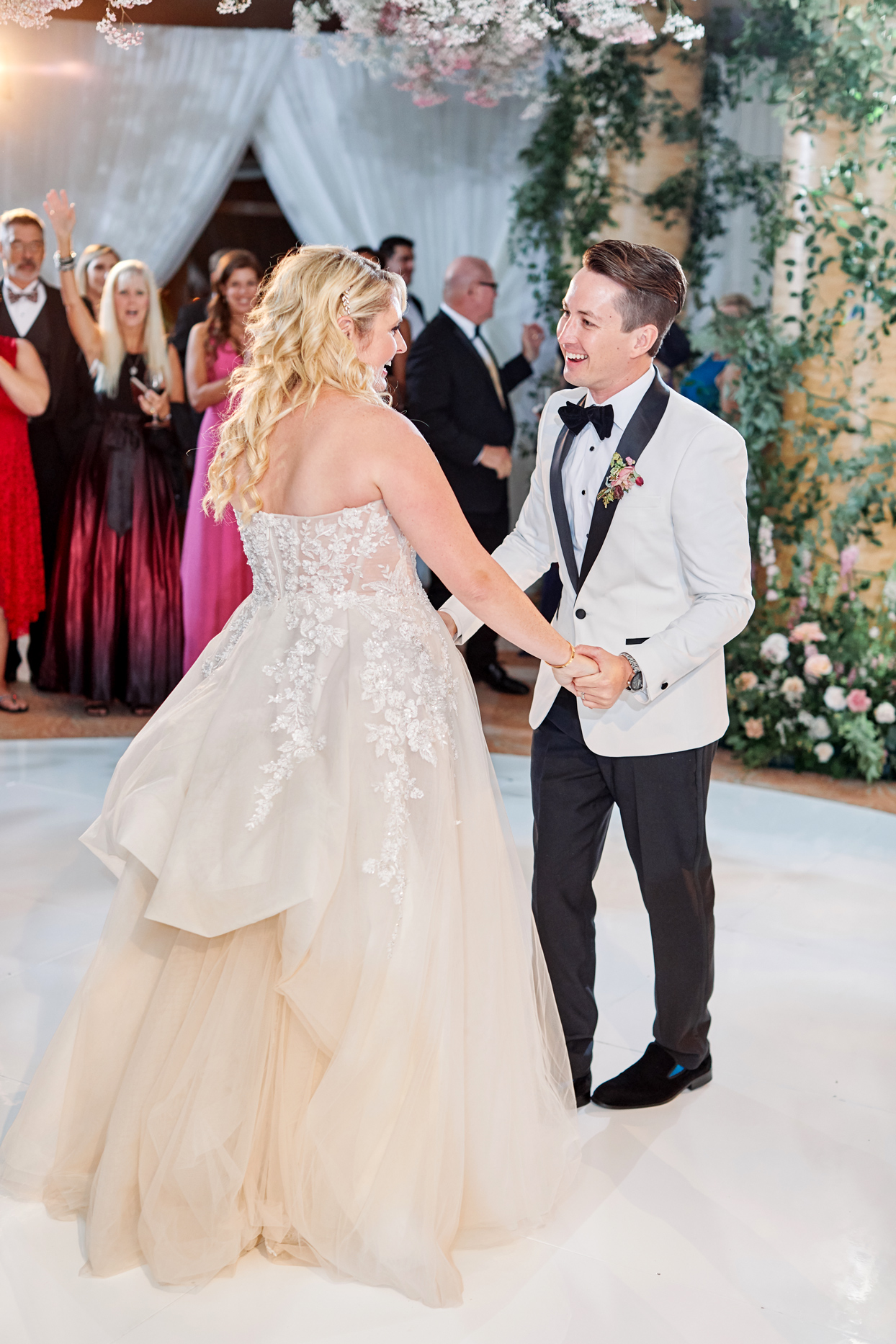 bride and groom smile holding hands during first dance on white dance floor