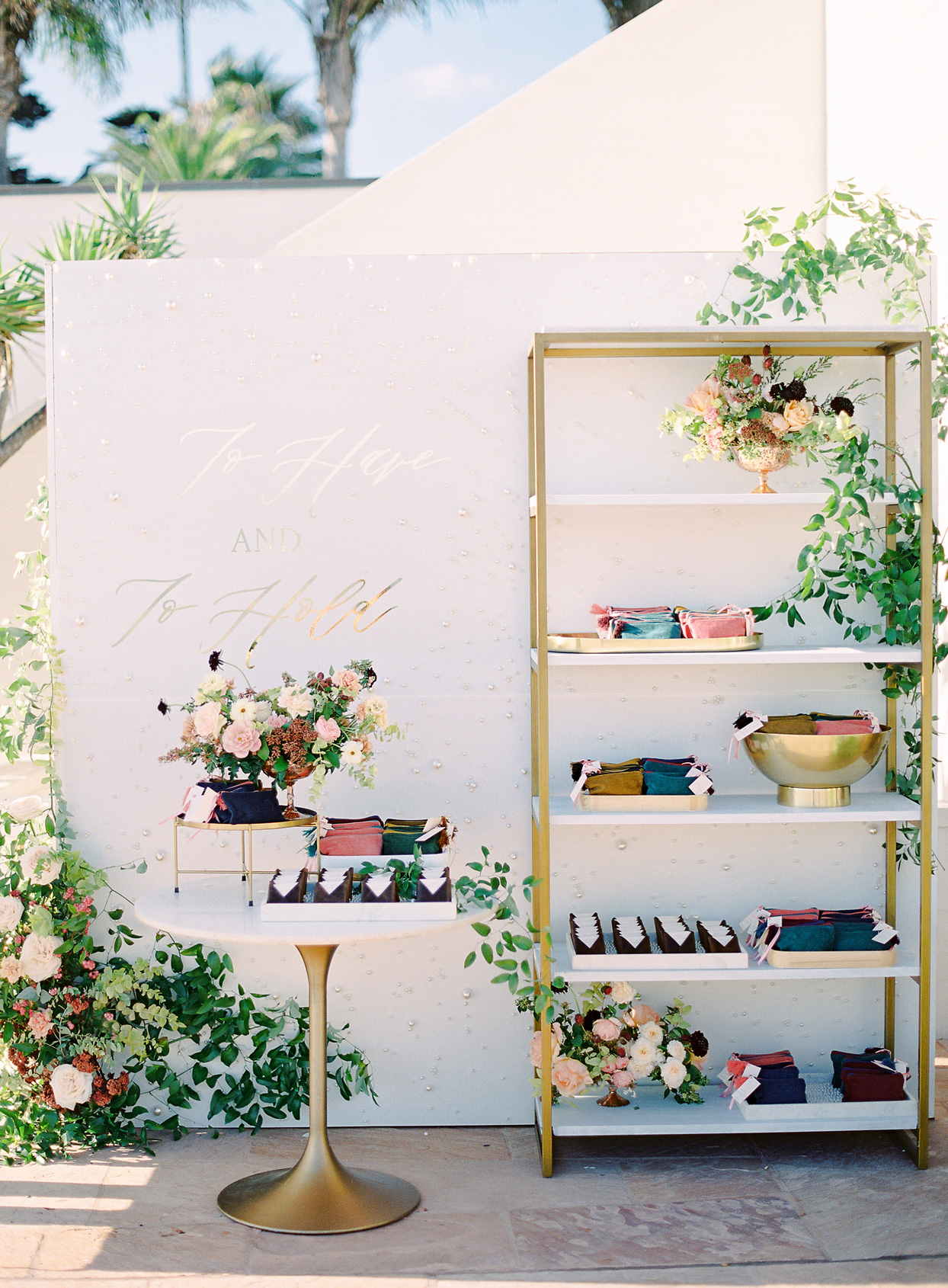 multi colored bags wedding favors on gold and white display tables and shelving