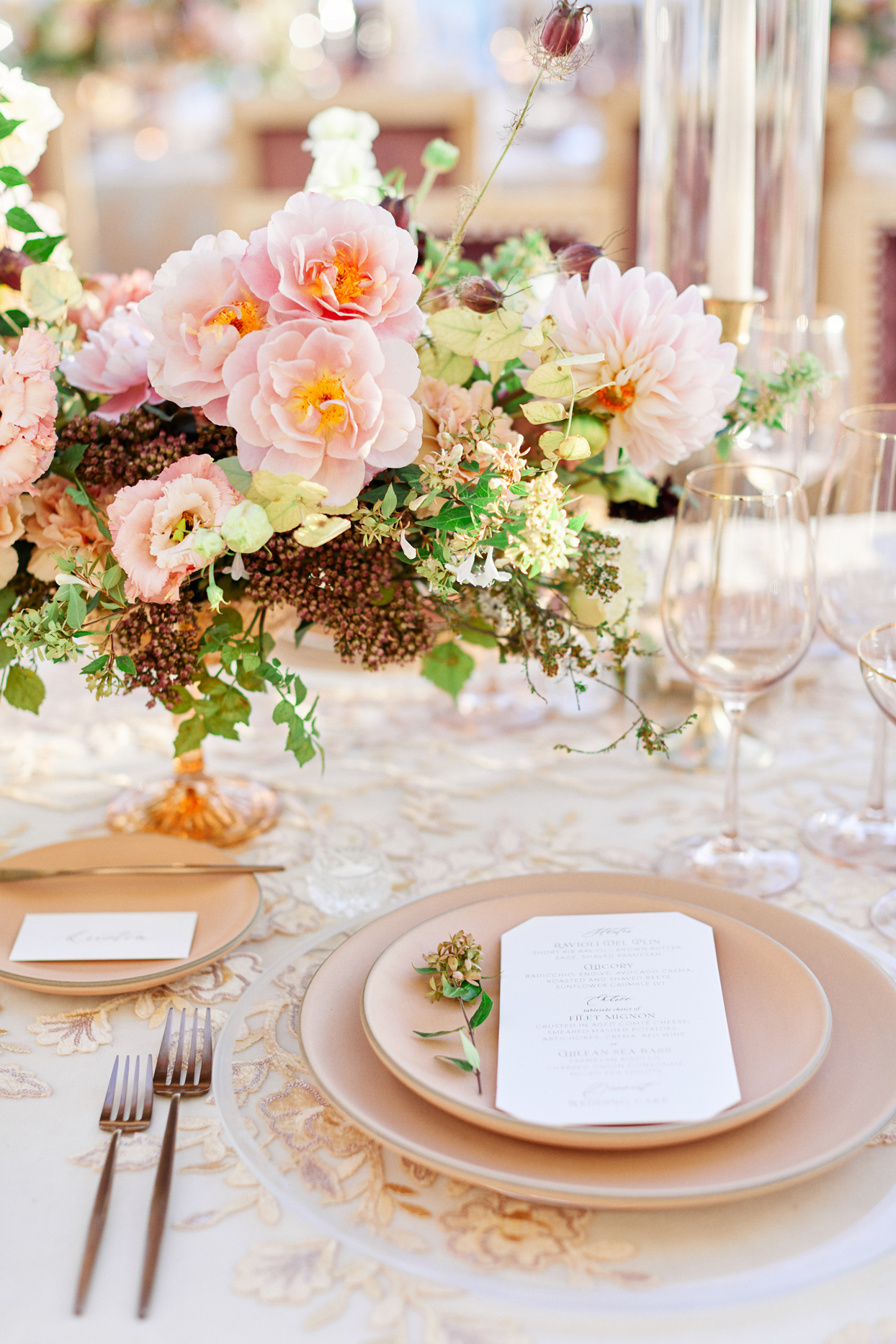 cream colored place setting with floral centerpieces