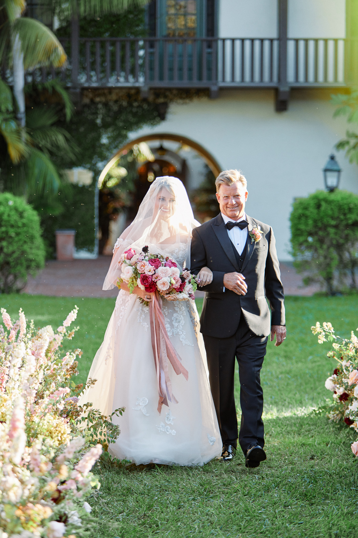 bride wearing vail walking down aisle with father outside