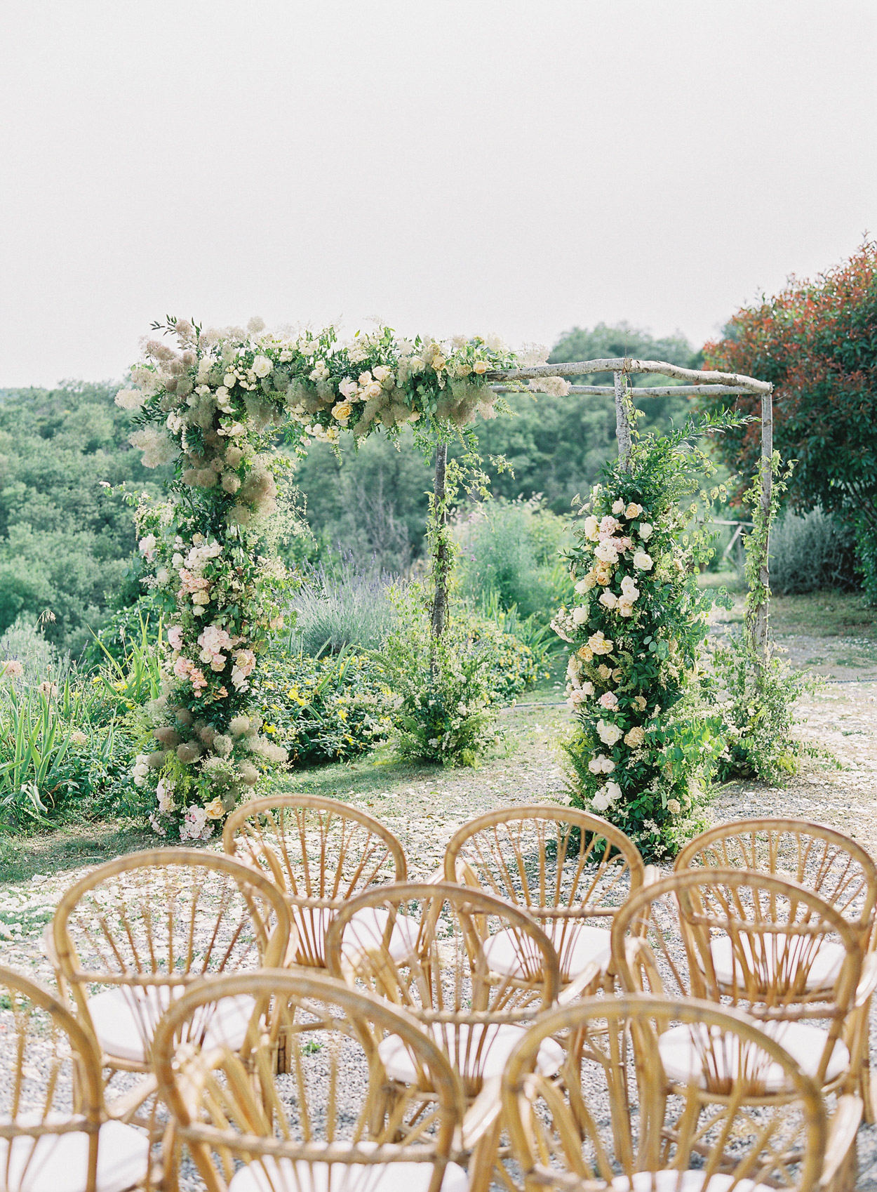 outdoor wedding space chairs facing arbor with greenery flowers