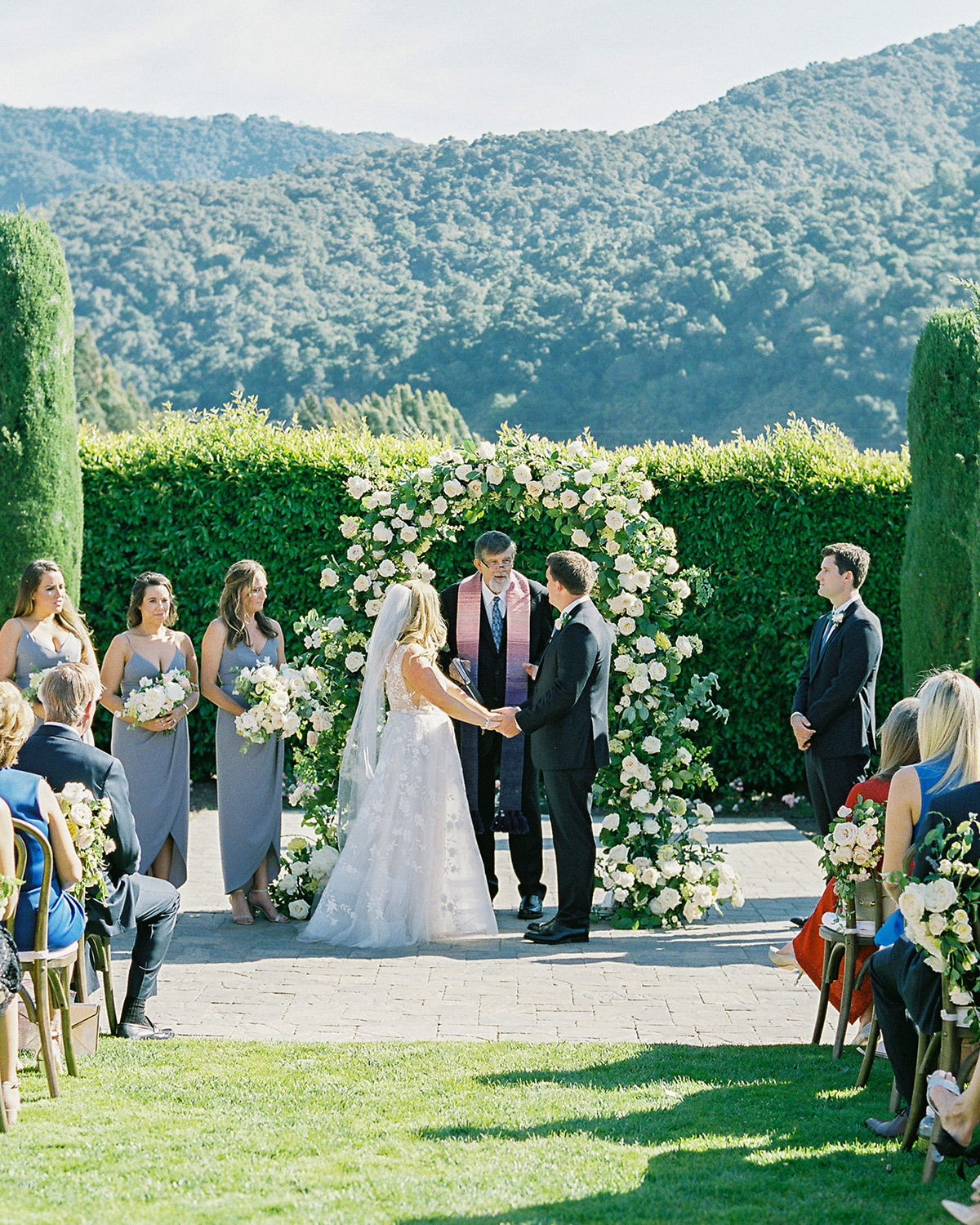 bride and groom exchange wedding vows during outdoor ceremony