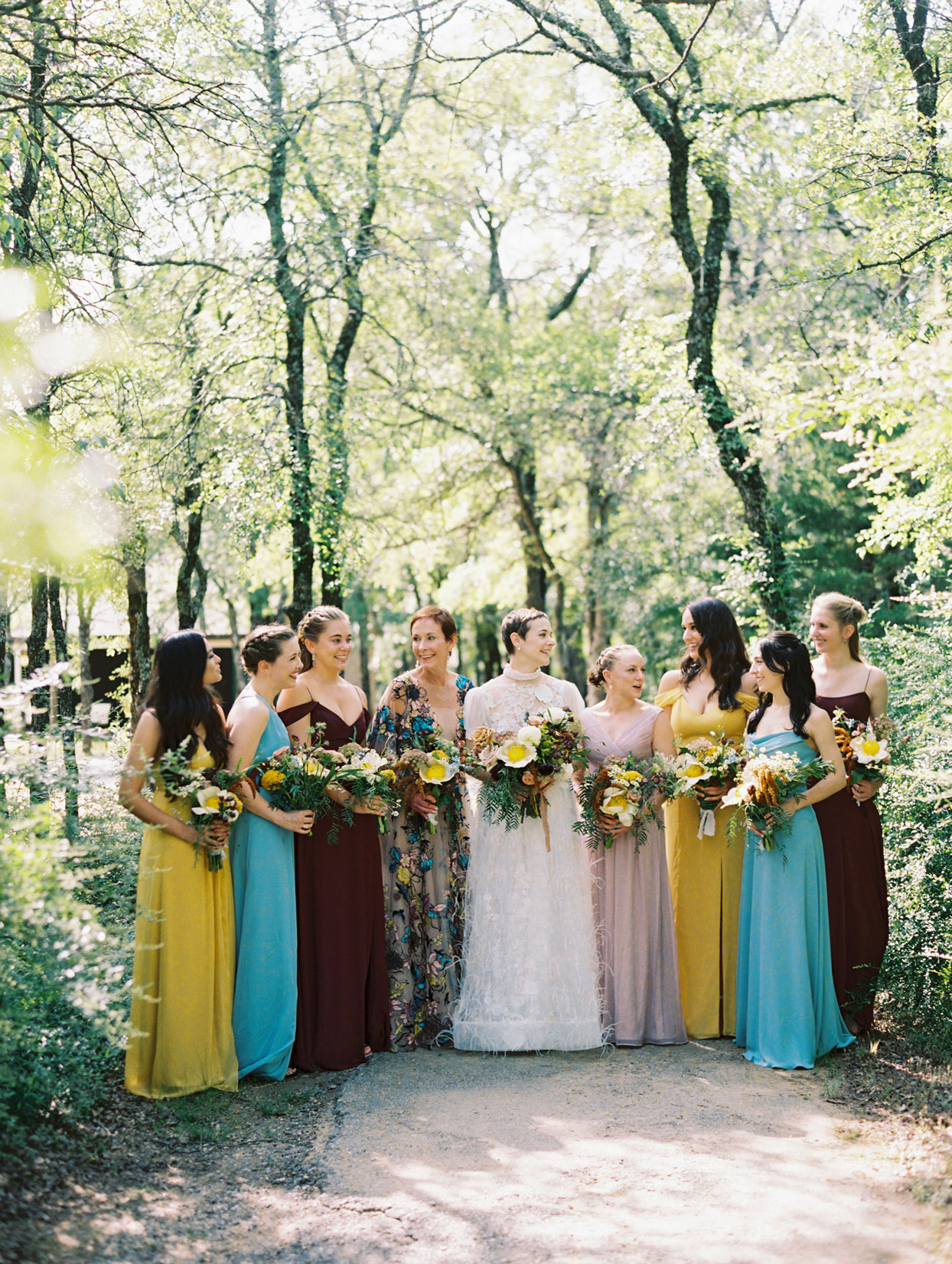 Bride with mother and bridesmaids in blue, burgundy, blush, and gold tones