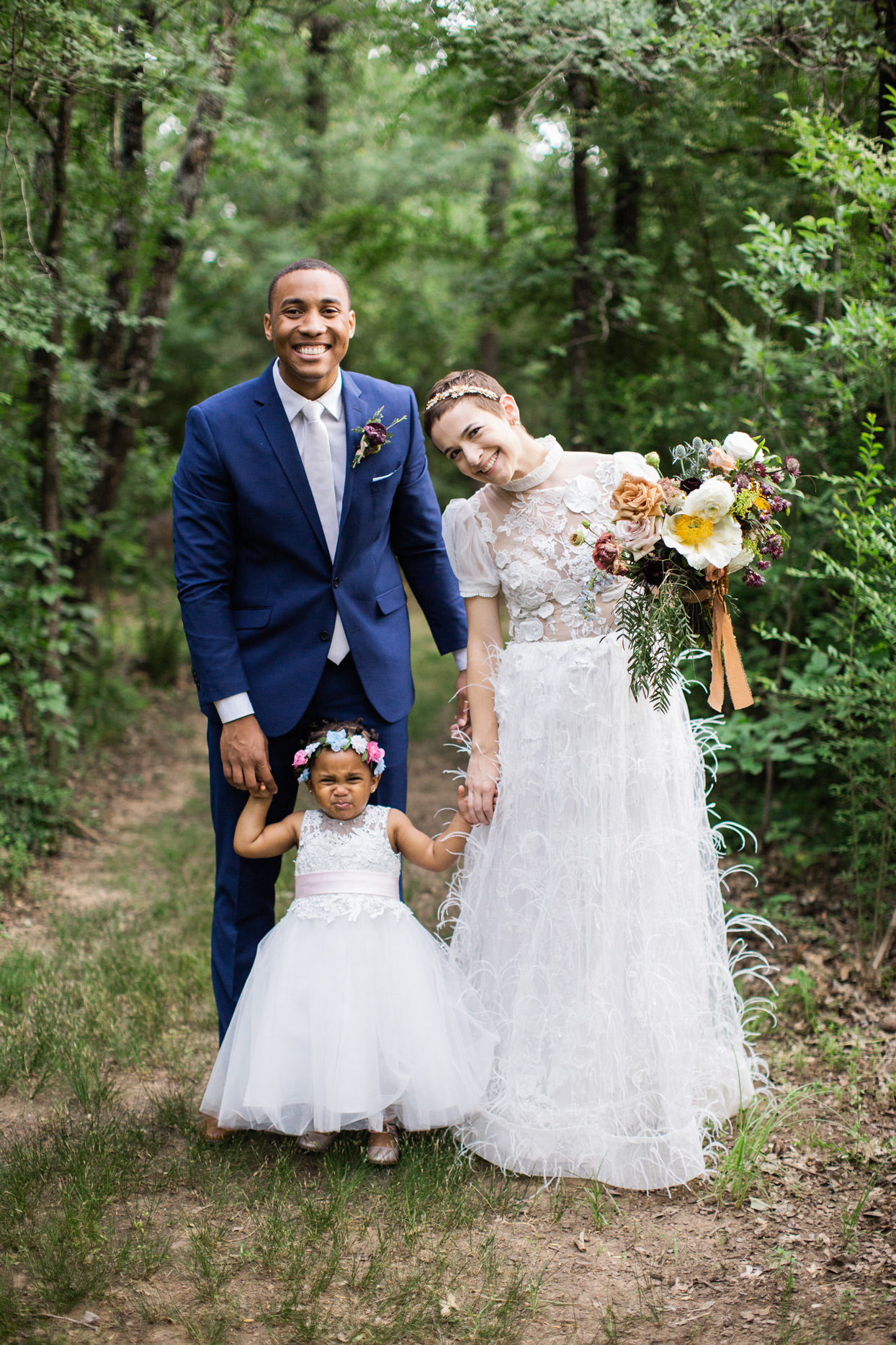 Groom, bride, and flower girl in wooded area