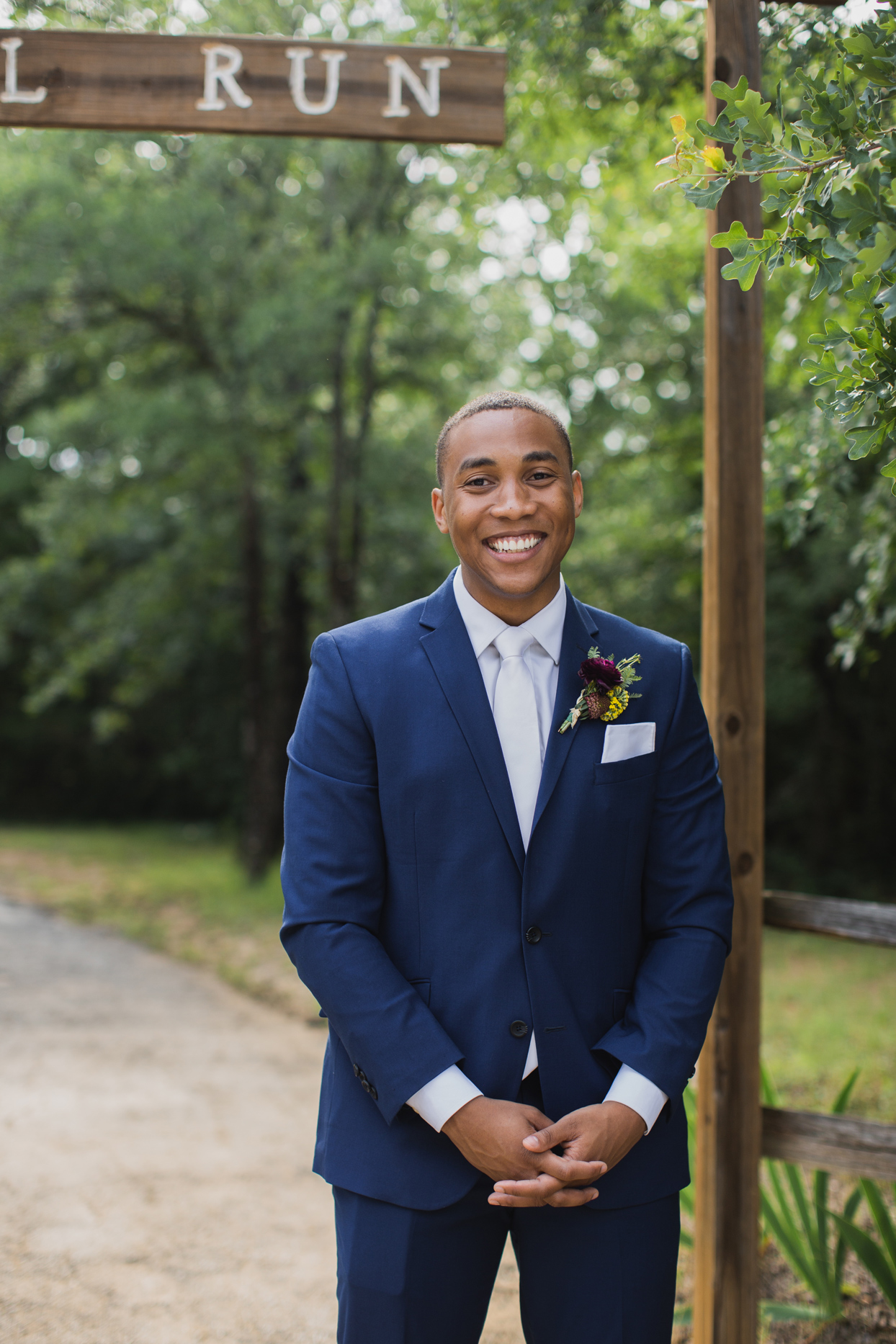 Groom standing outside in blue suit