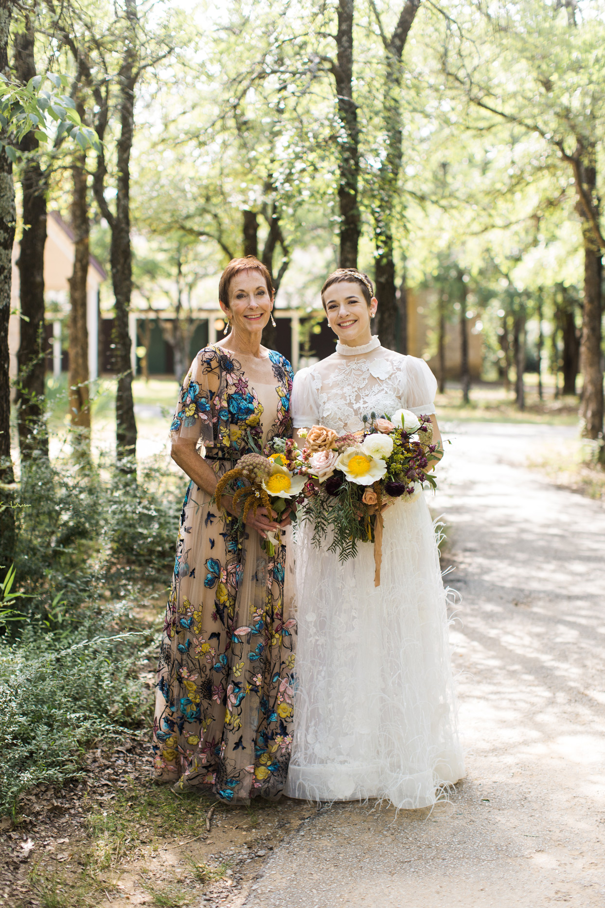 Bride with mother in wooded area