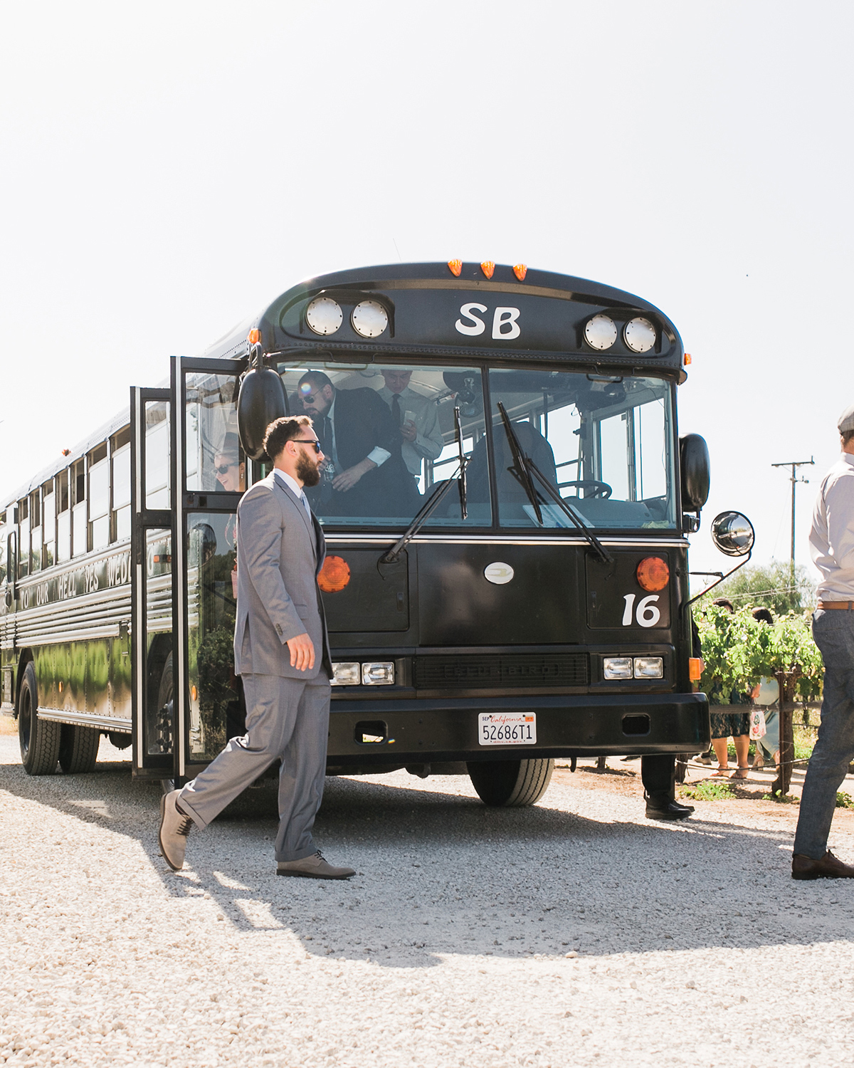 guests getting out of black wedding bus