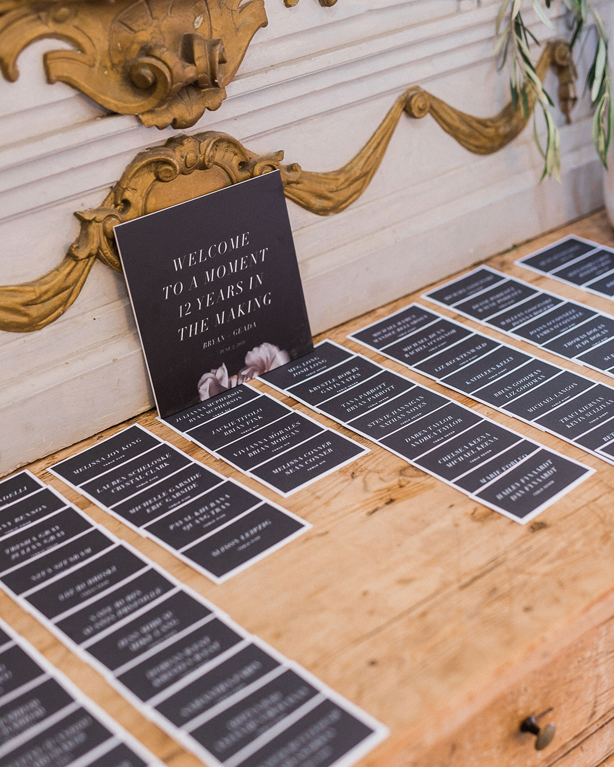 black and white type printed wedding escort cards on wooden table