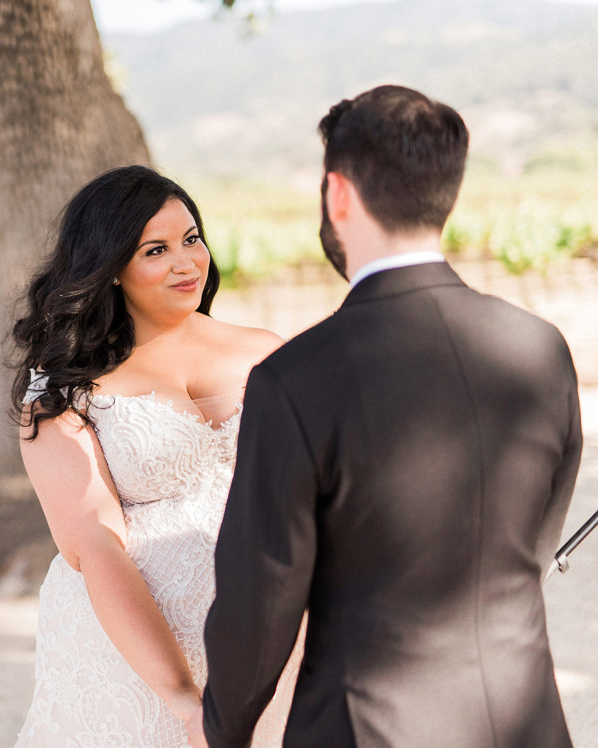 bride smiling at groom outside during first look