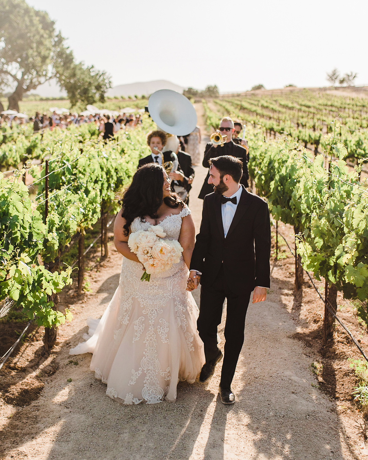bride and groom walk through vineyard with band and guests behind them