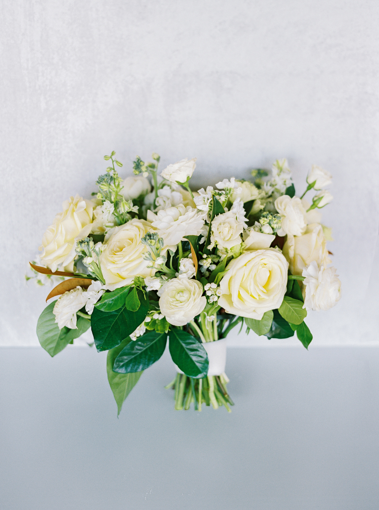 all-white floral wedding bouquet with white ribbon