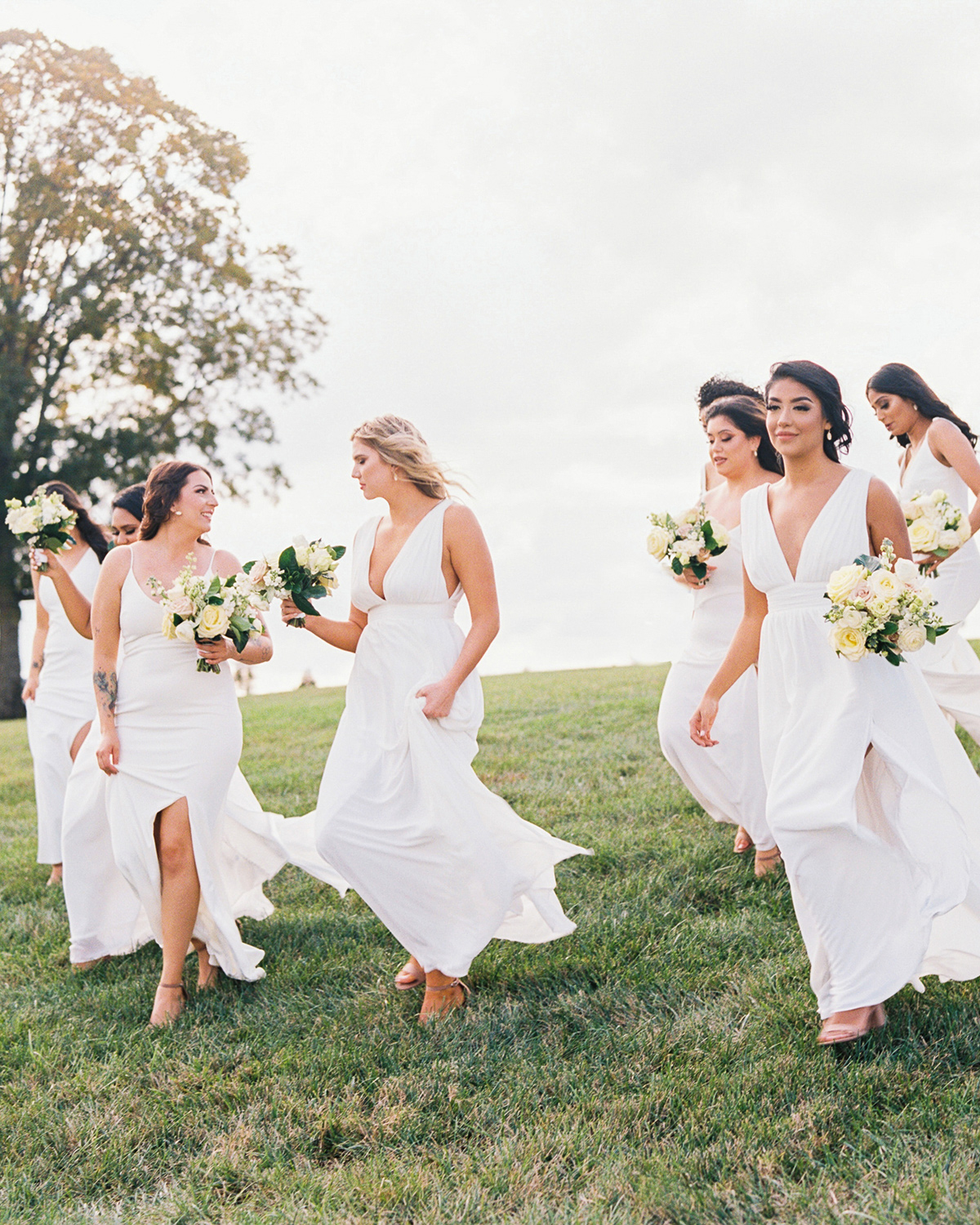 bridesmaids in white long dresses walking down grassy hill