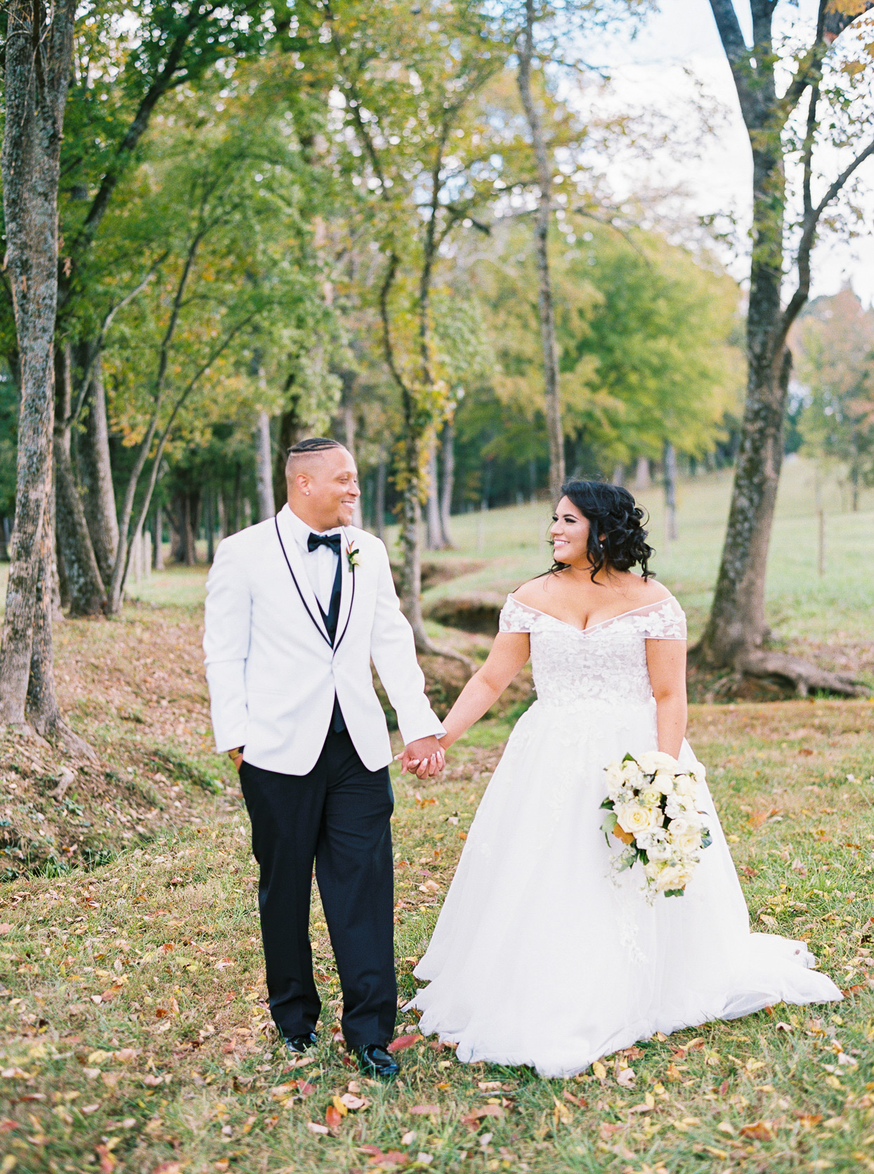 bride wearing off-the-shoulder sweetheart neckline lace a-line wedding dress holding hands with groom outside