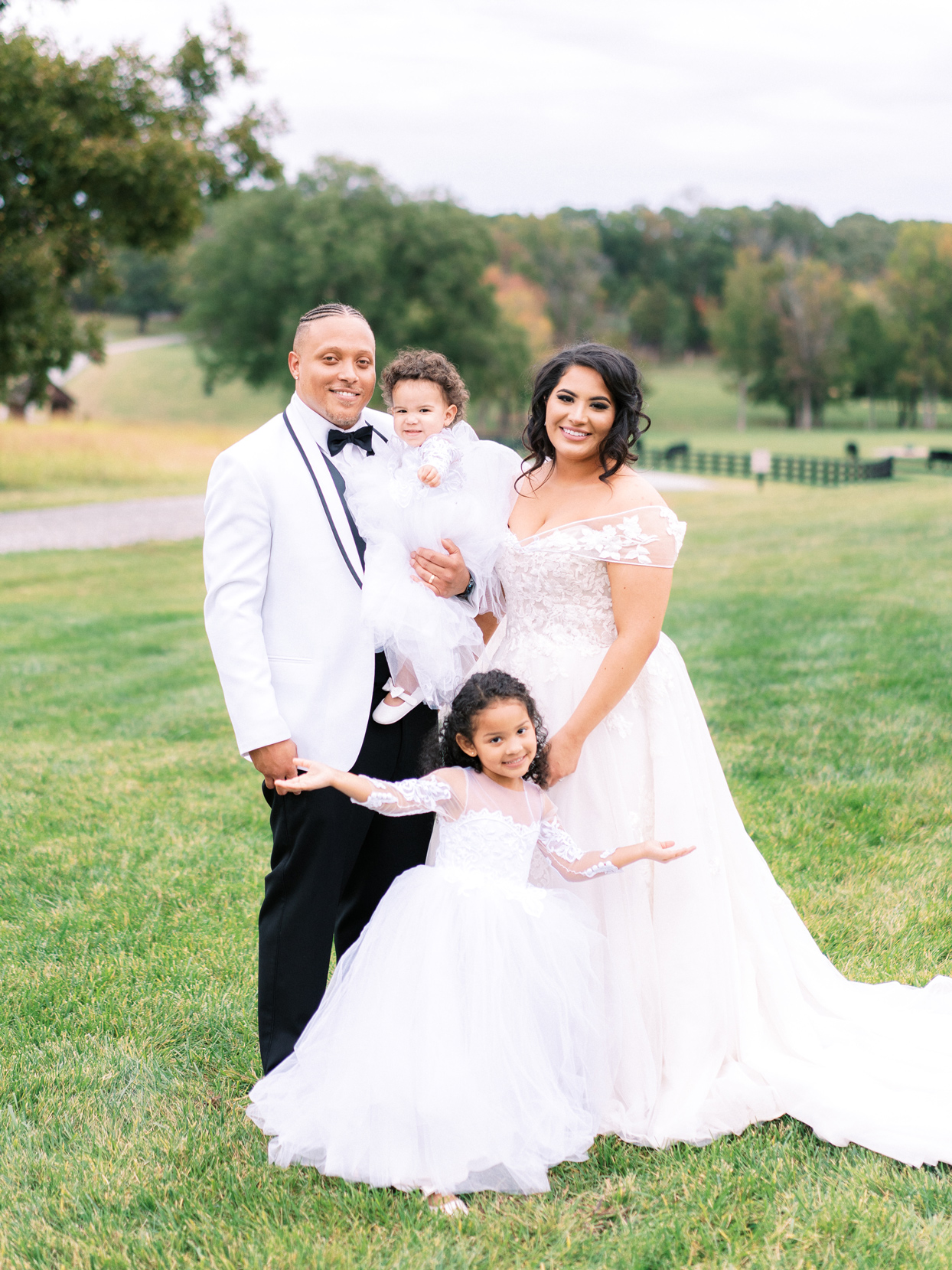bride and groom stand smiling with two daughters