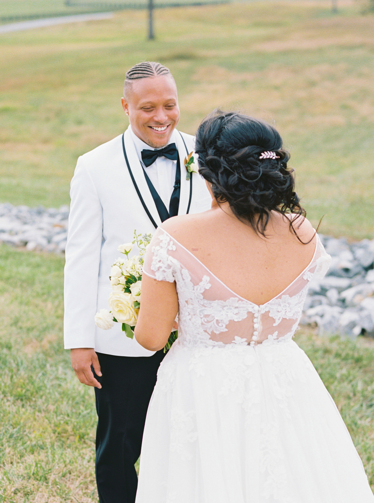 groom smiling at bride outside during first look