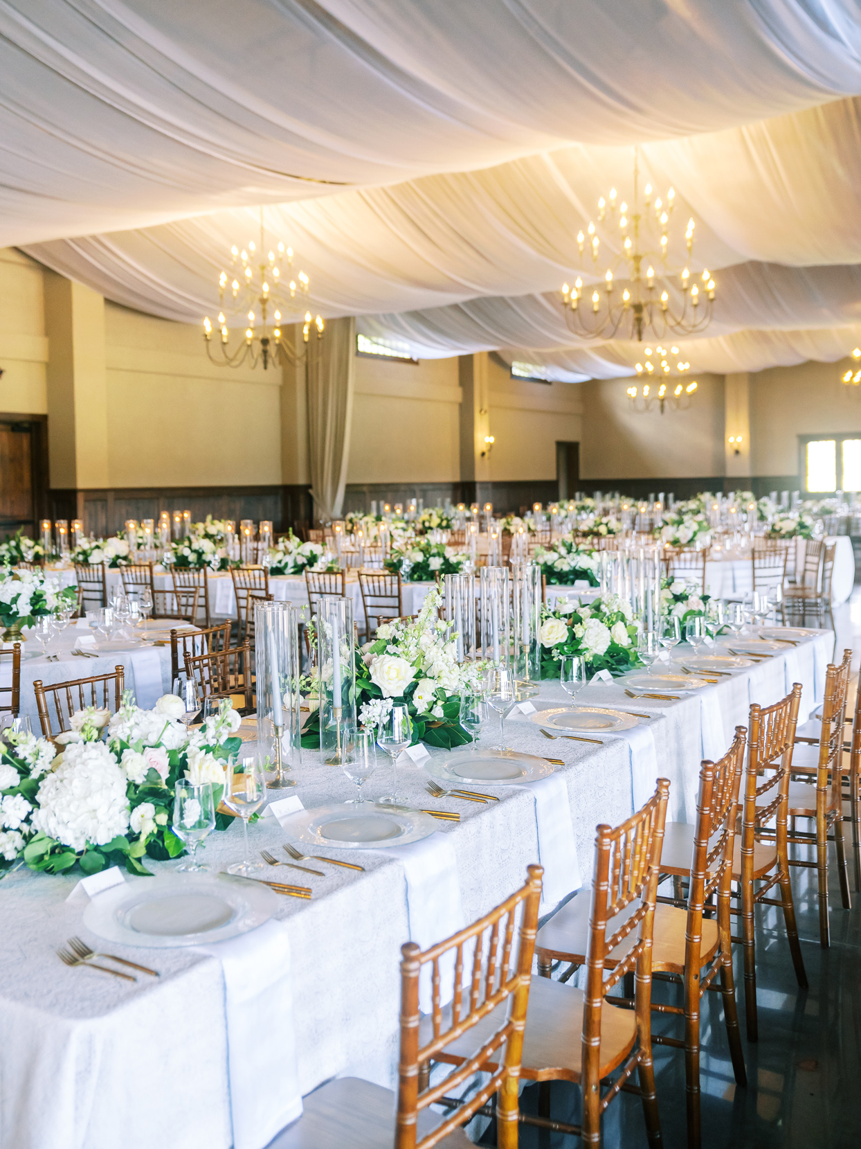 white floral and greenery table centerpieces on long reception tables
