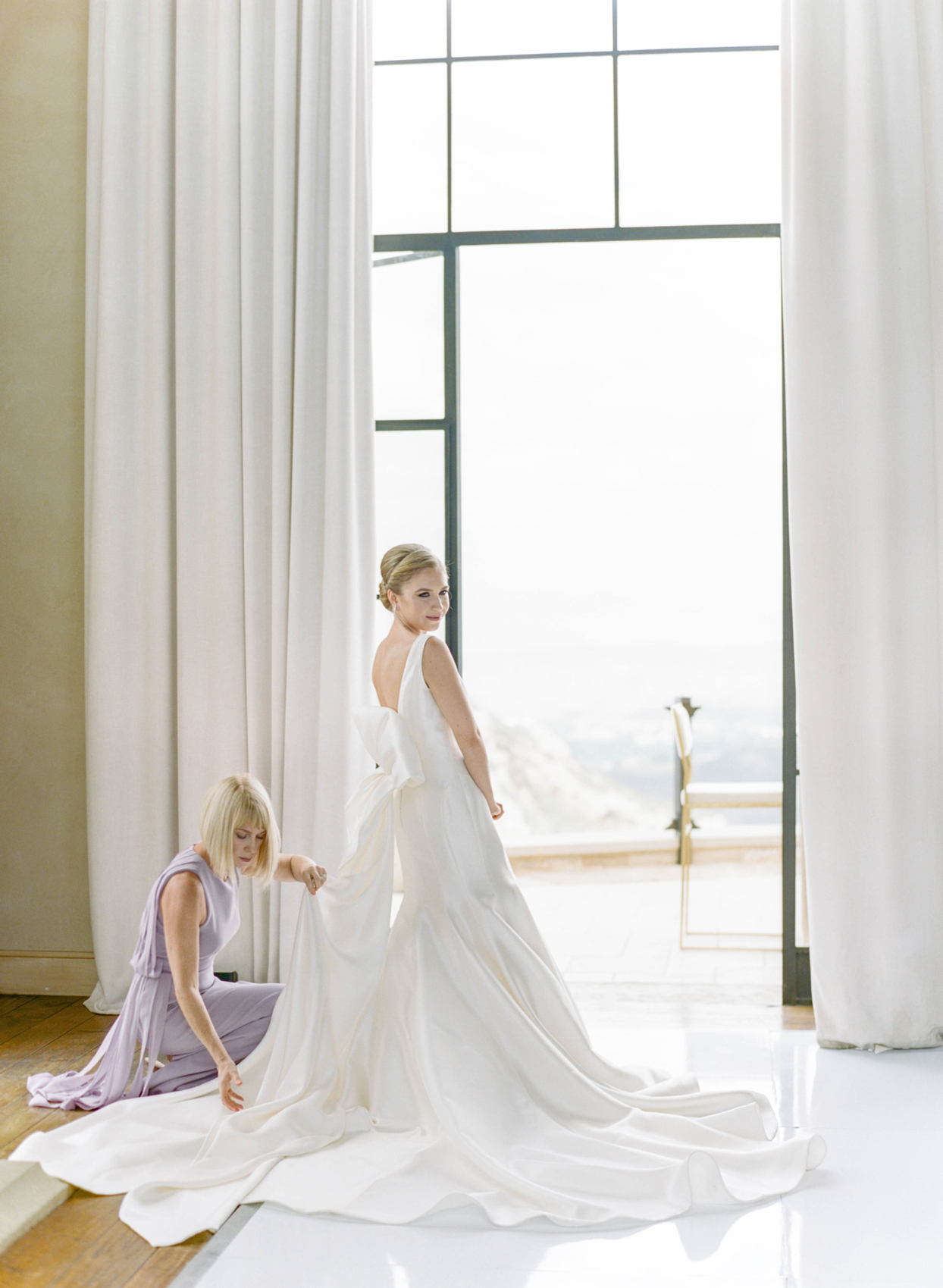 bride standing in front of window with woman adjusting train of gown