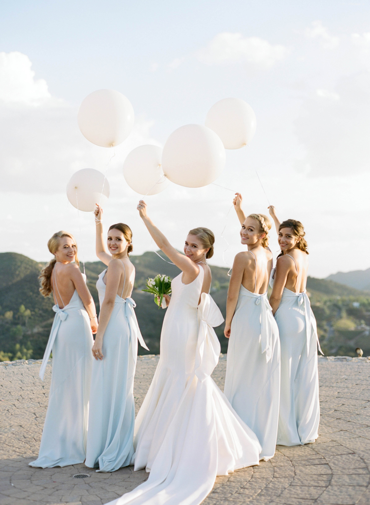 bride and bridal party holding white balloons