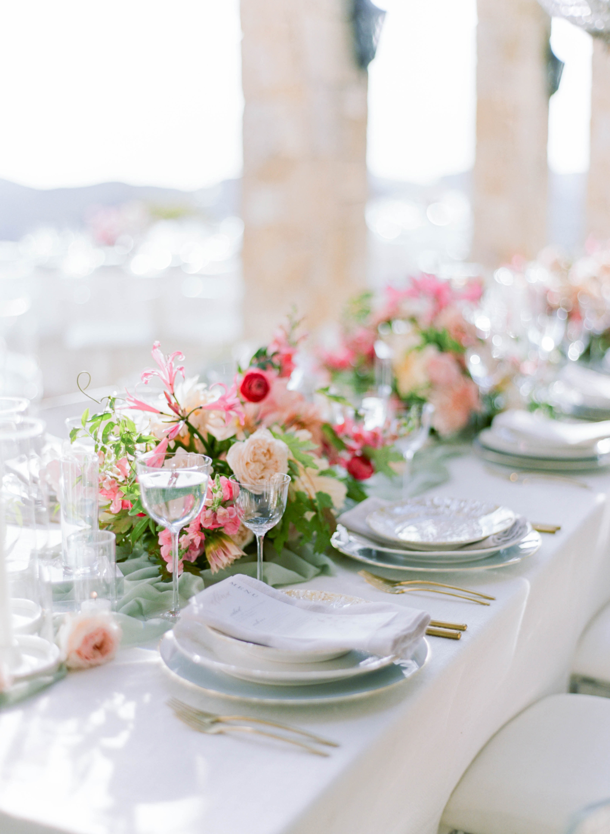 white table settings with pink floral centerpieces