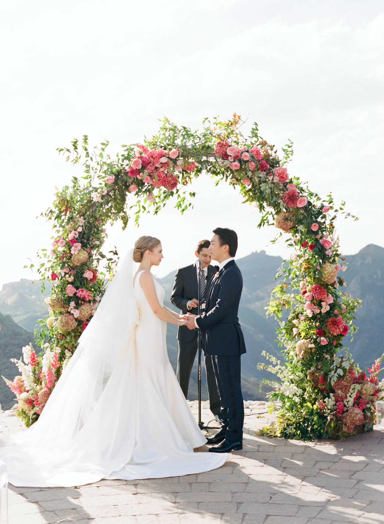 bride and groom holding hands beneath floral ceremony arch