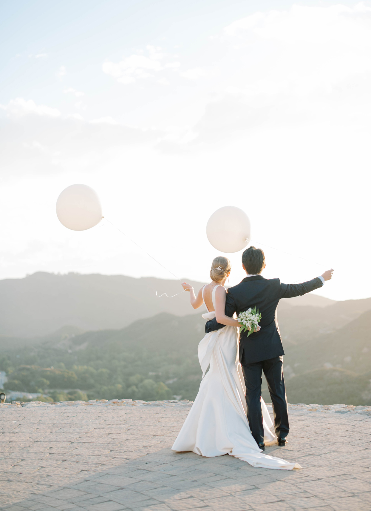 bride and groom holding white balloons