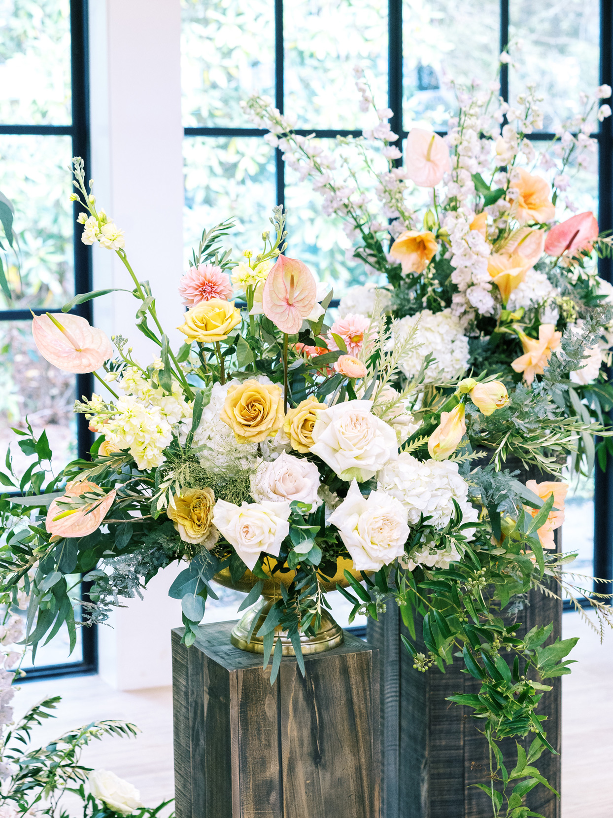 Large urns with roses, hydrangeas, and other dramatic blooms