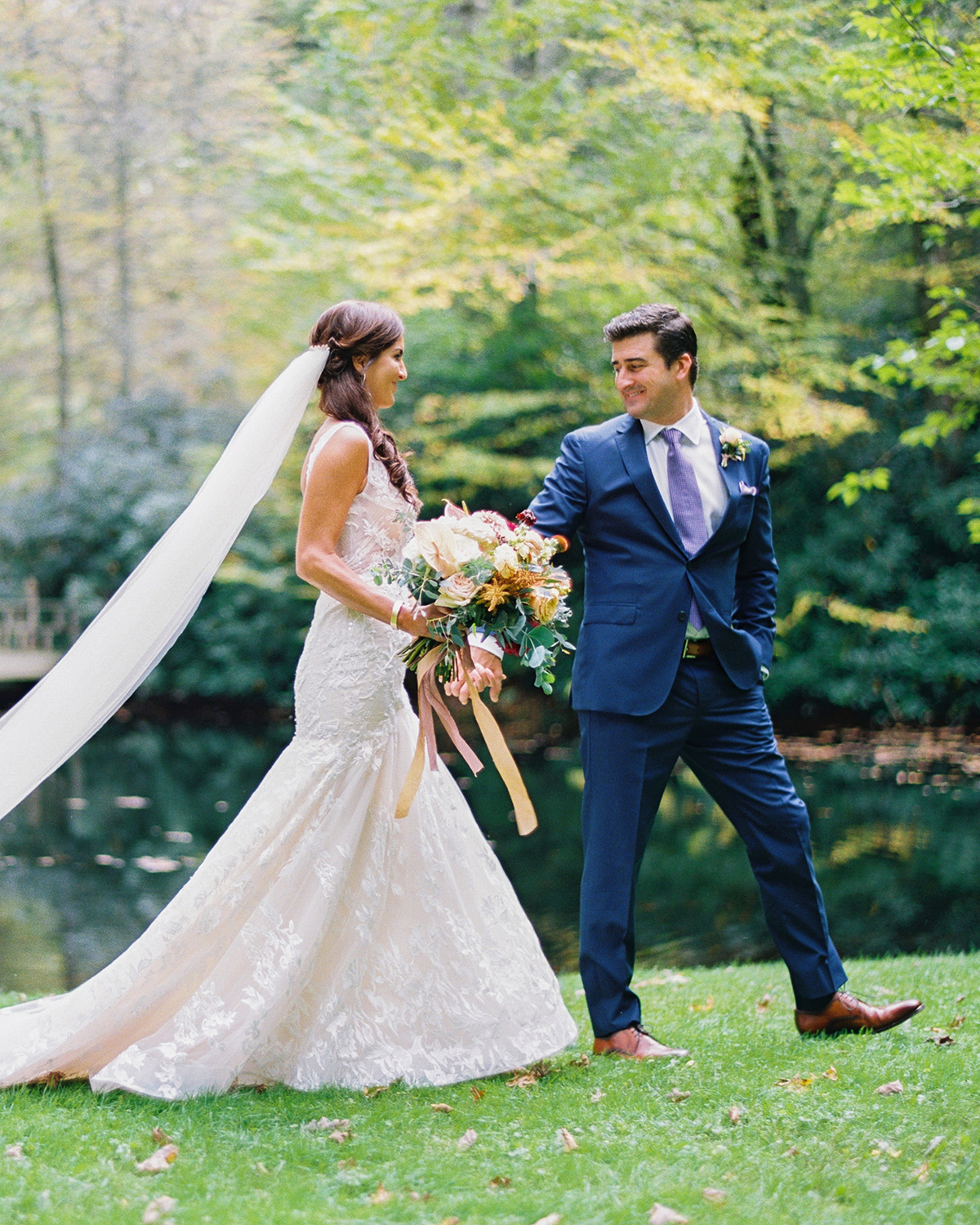 Bride and groom walking together in grass