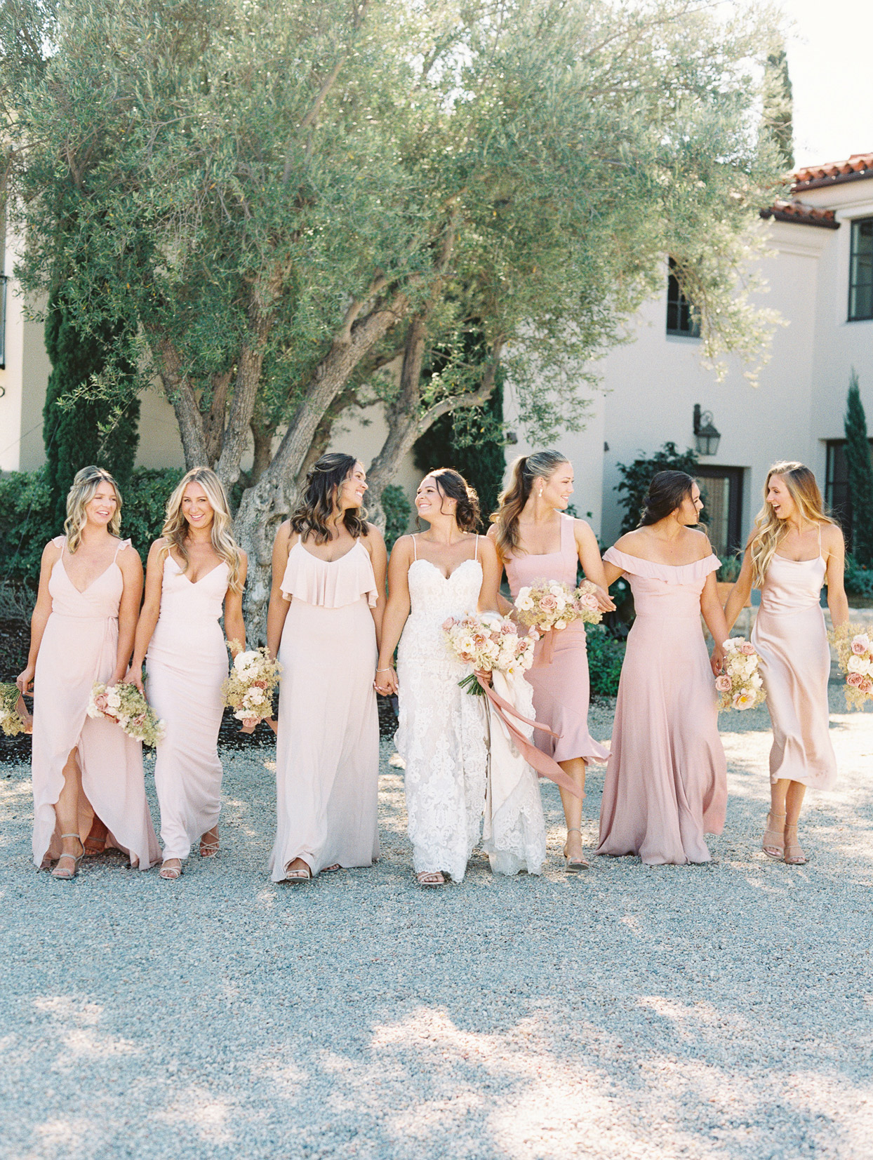 Bride with bridesmaids wearing soft pink tone dresses