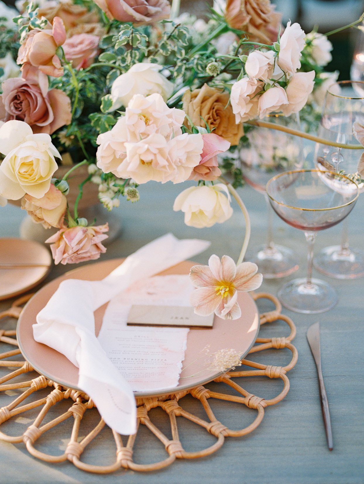 Place settings with blush colored plates and gold-rimmed glassware, and copper flatware