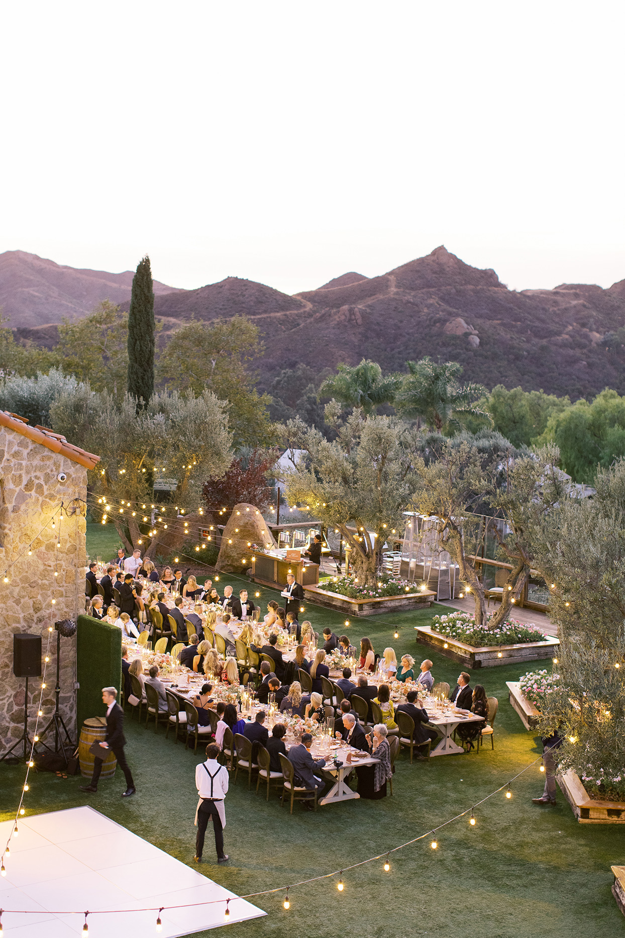 Outdoor wedding reception space with two long tables and string lights