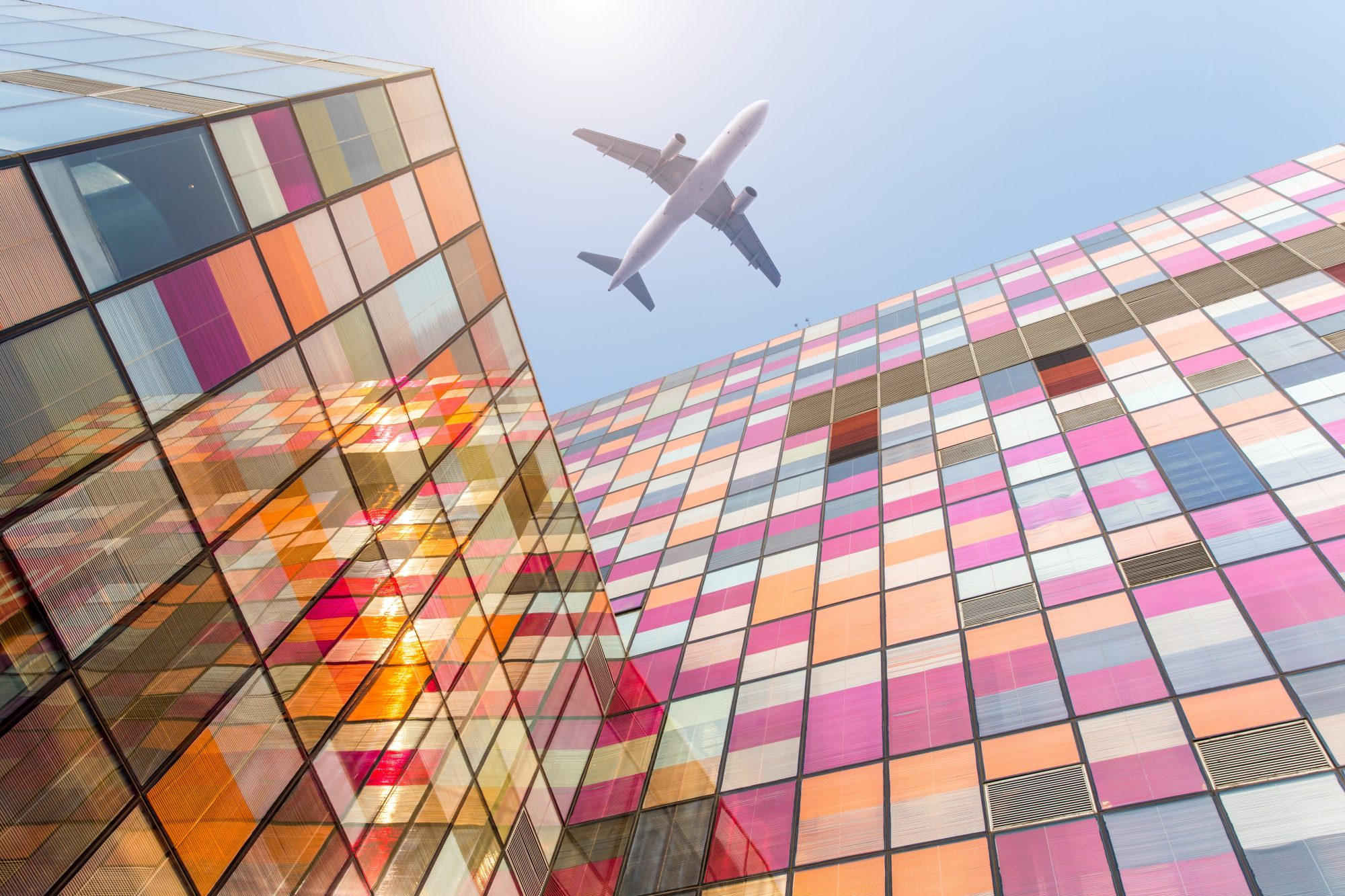 airplane flying over a colorful glass building