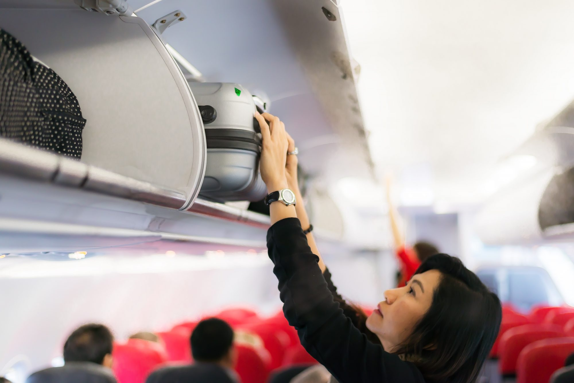 woman putting luggage in overhead bin