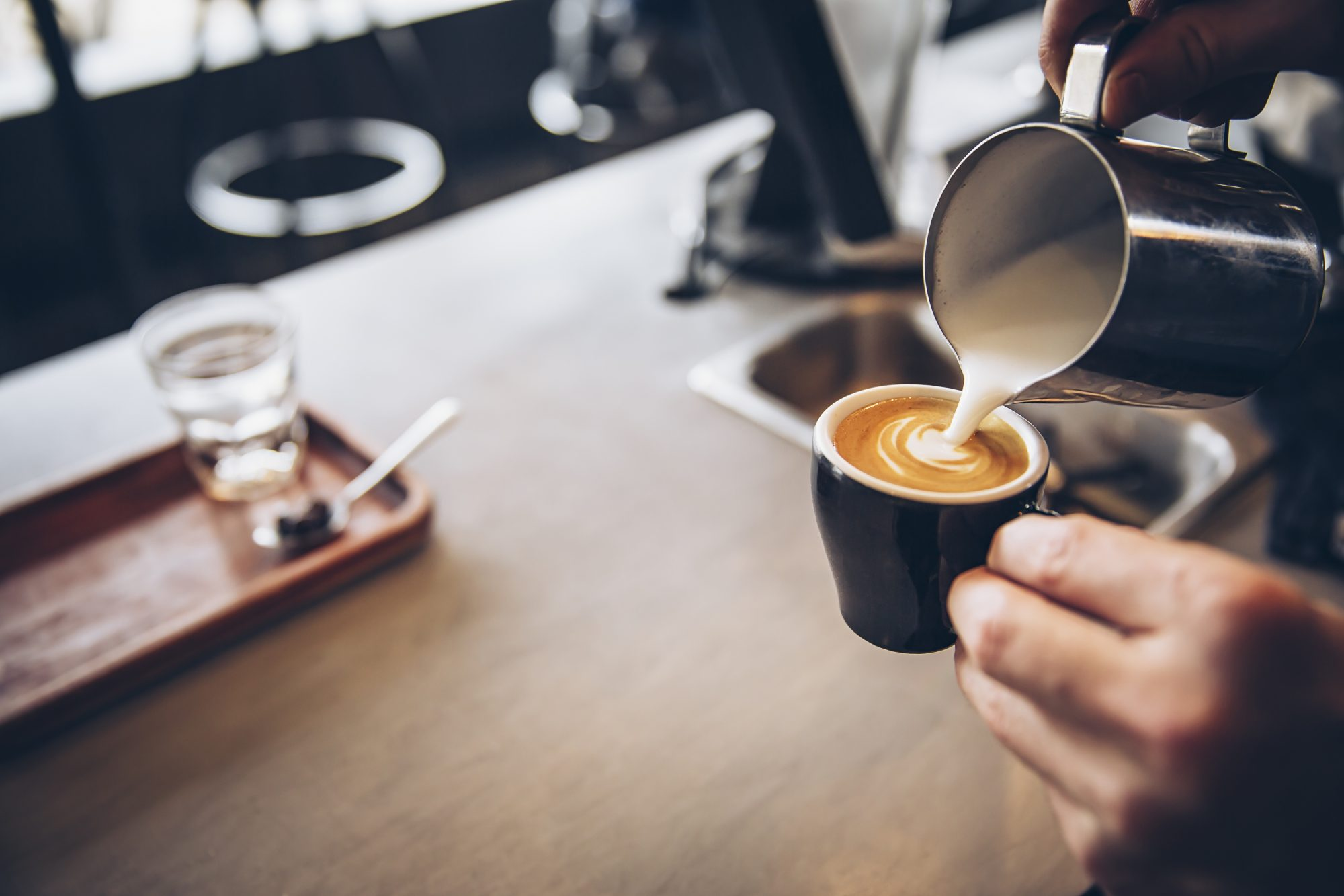 barista pouring coffee in cafe