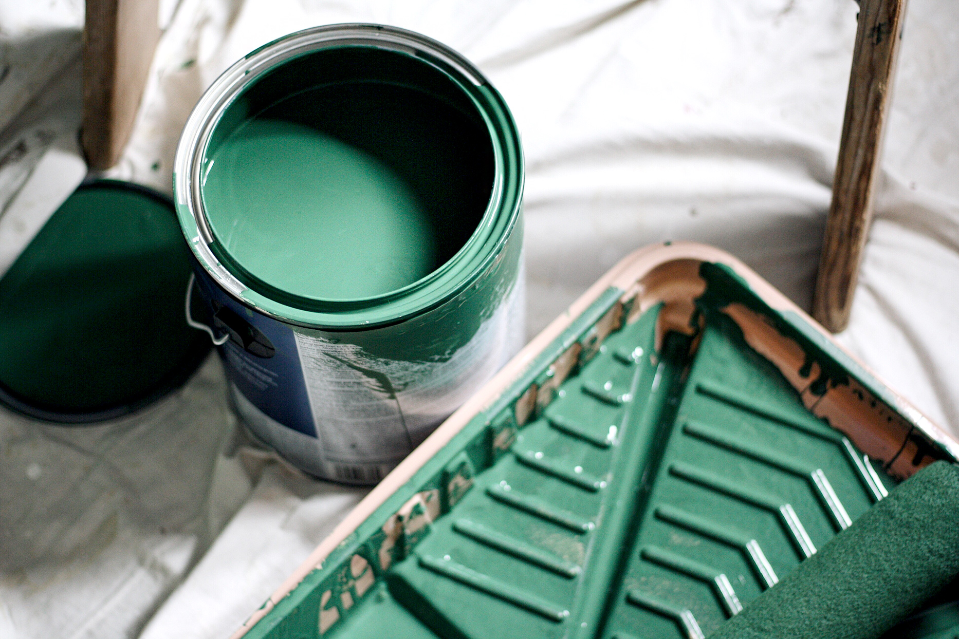 Dark green paint can with paint supplies