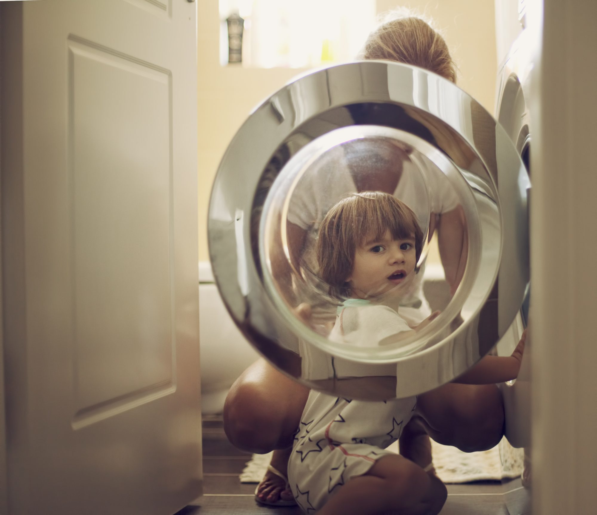 Small boy with his mother in front of a washing machine