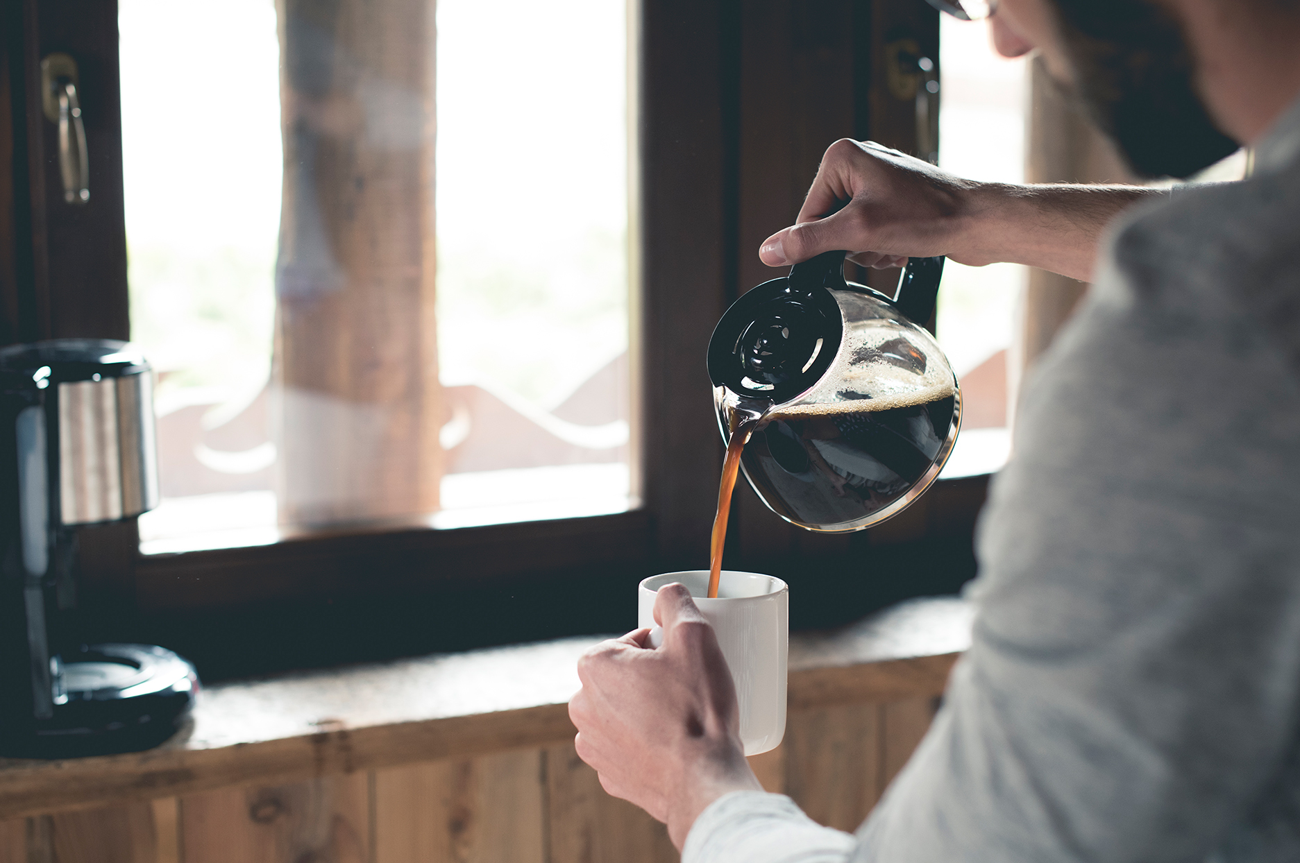 Person pouring coffee in kitchen in front of window