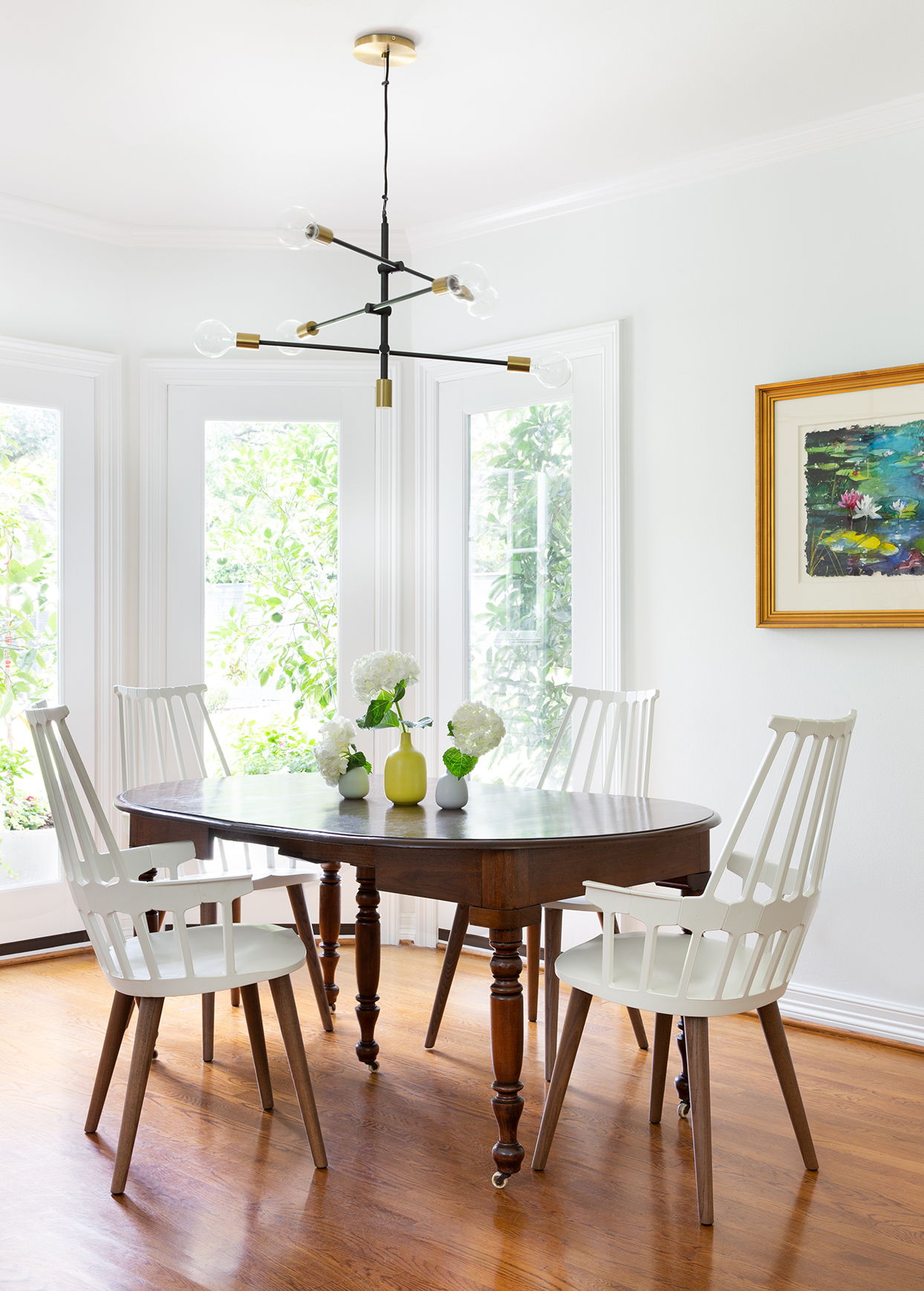 breakfast nook with wood table and white chairs and natural light