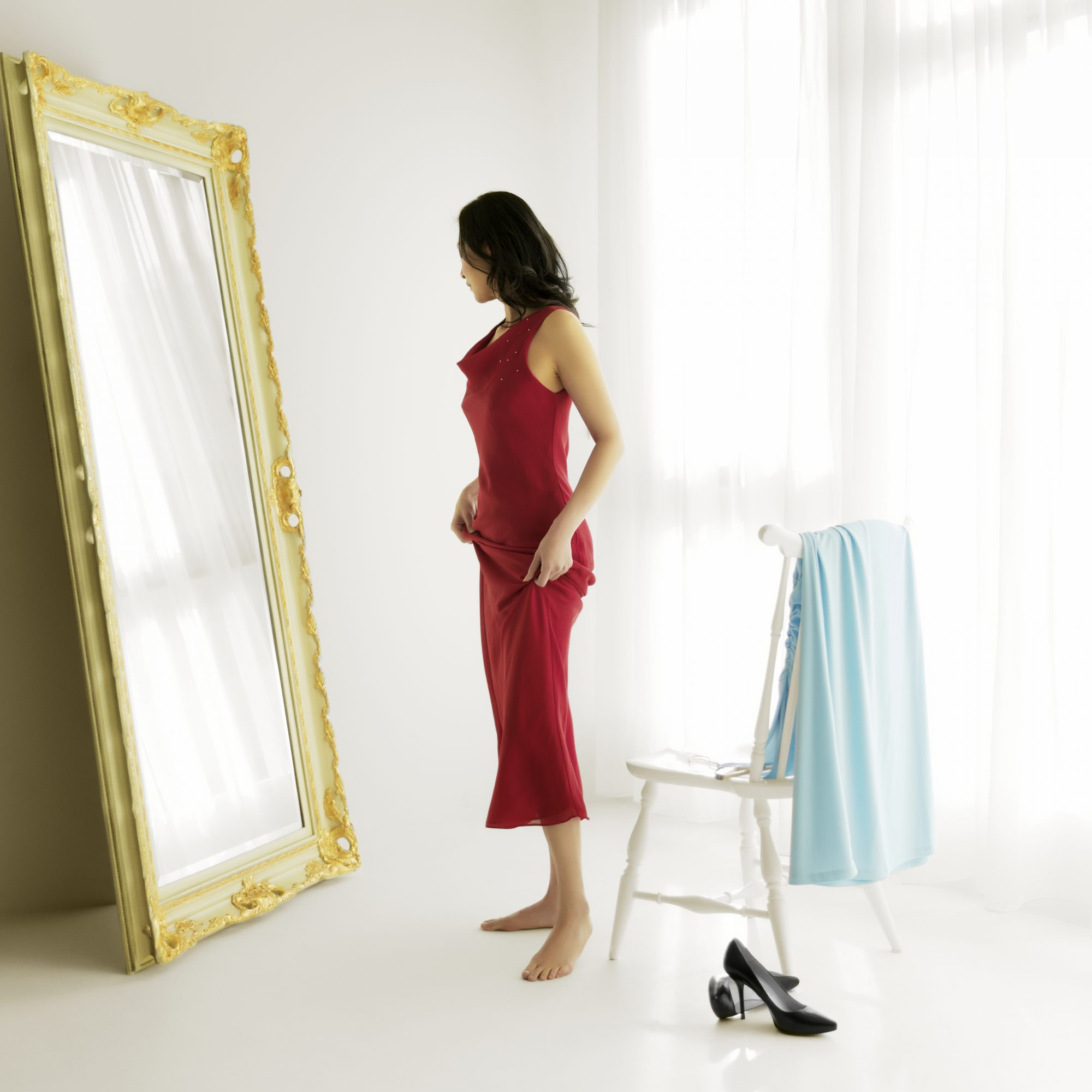 Side view of woman looking at her reflection through a full-length mirror while trying on different evening gowns or formal wear of designer clothing. She is barefoot with high heels on floor beside wood chair and fashion dress hanging over.