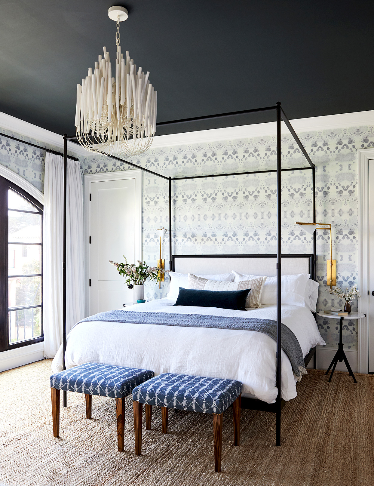 Bedroom with textured wallpaper and blue and white bed