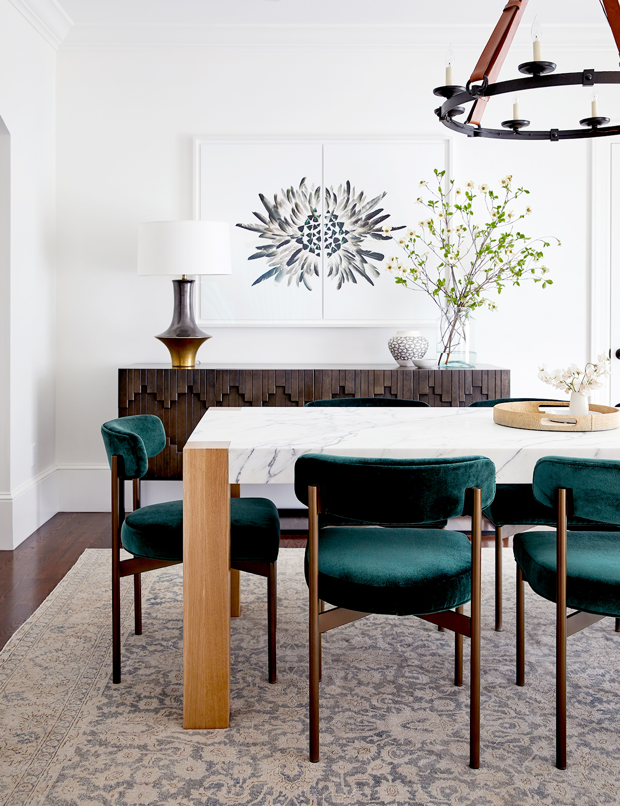 Dining area with marble table top and dark green chairs