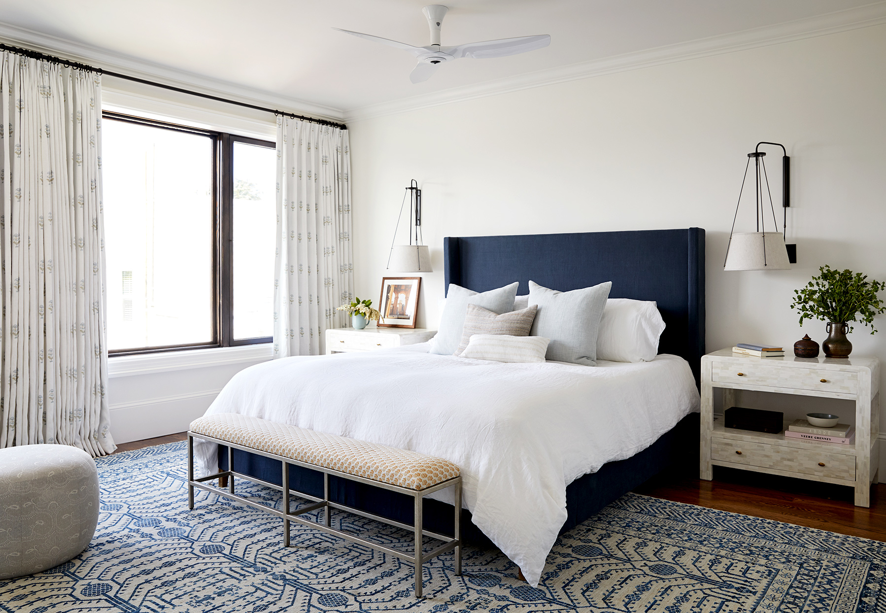 Bedroom with dark blue headboard and white comforter
