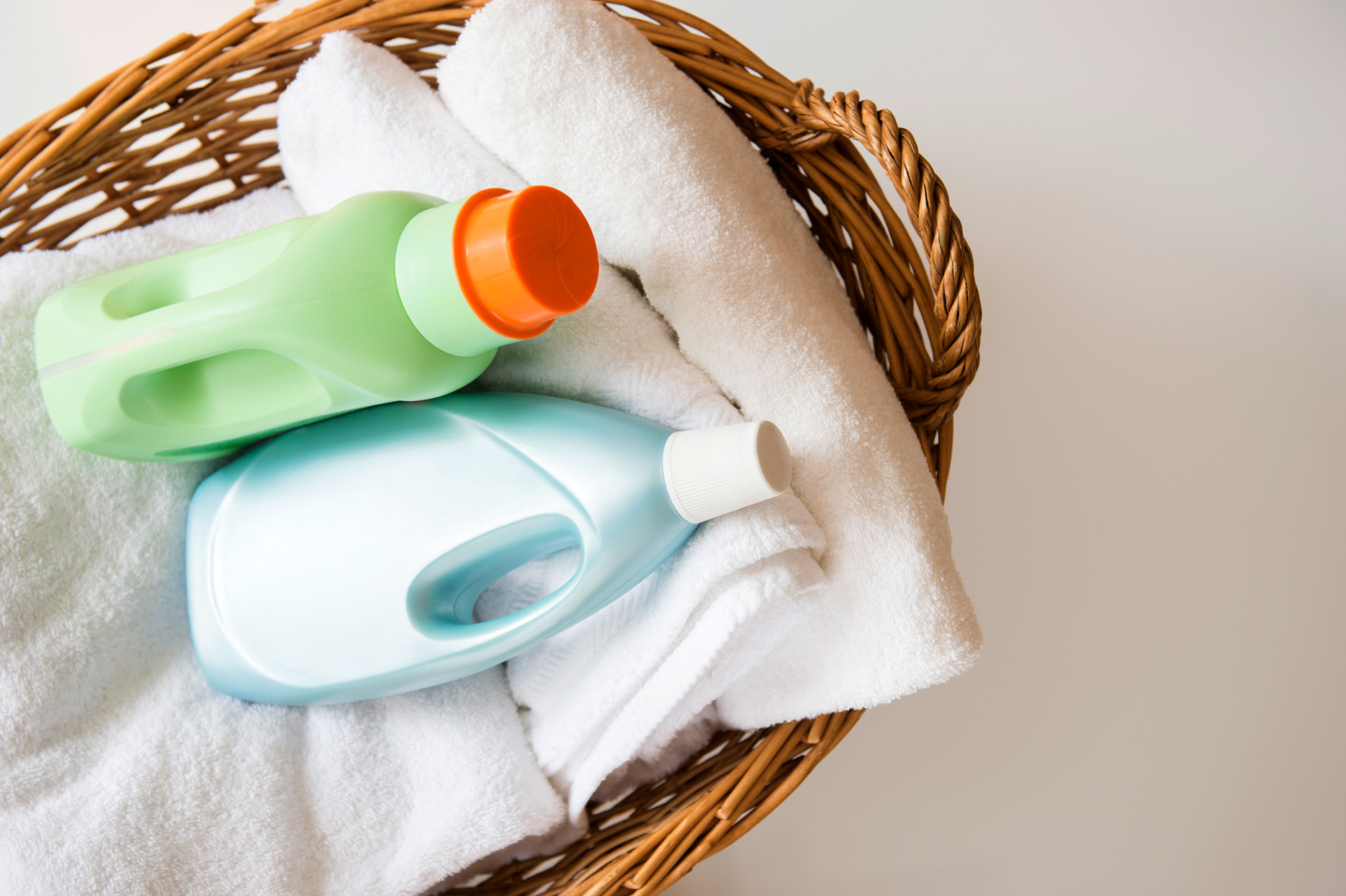 wicker basket filled with white towels and laundry detergent bottles