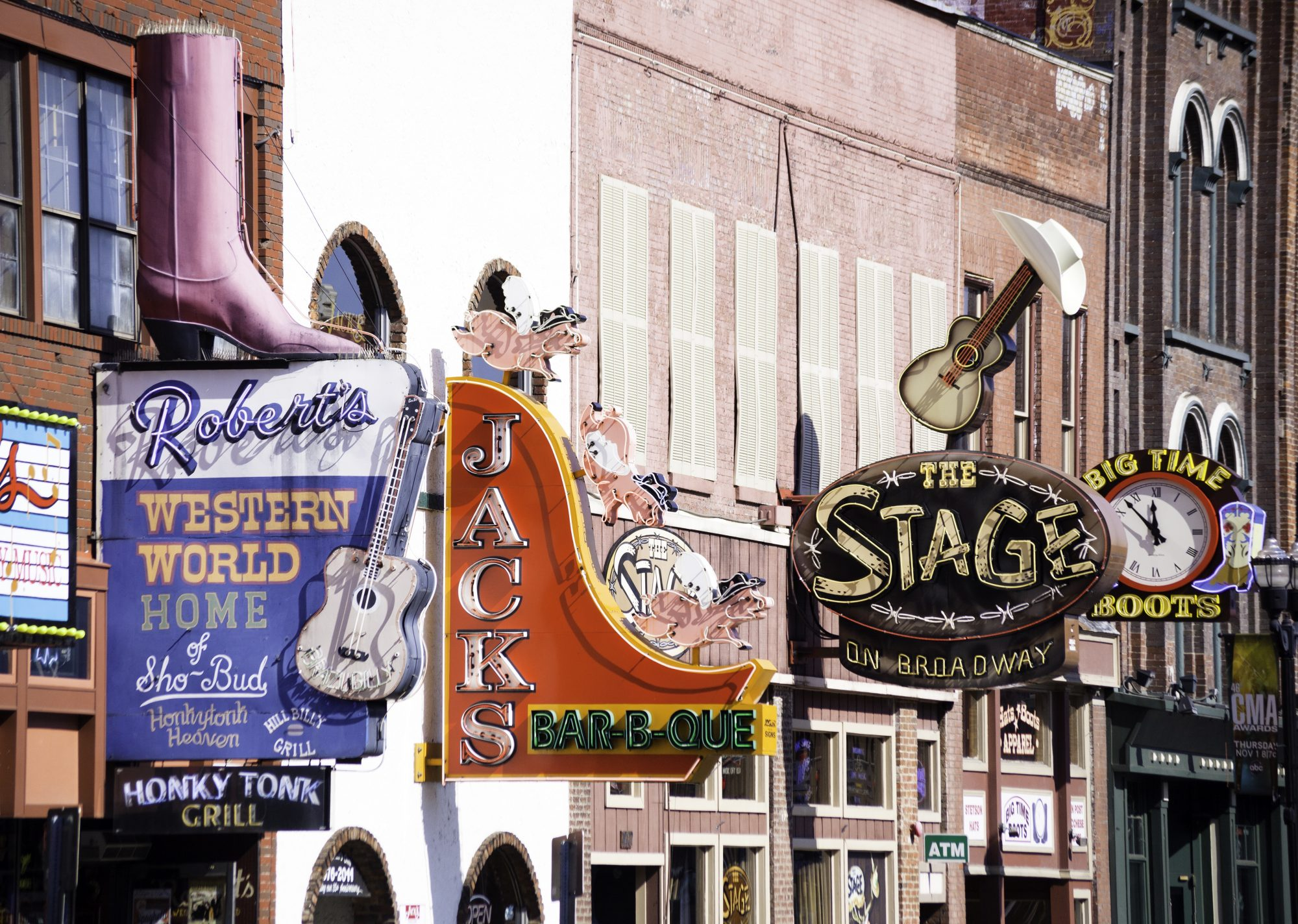 different colorful signs identificates shops and Honky Tonk bars located on Broadway Street in Nashville