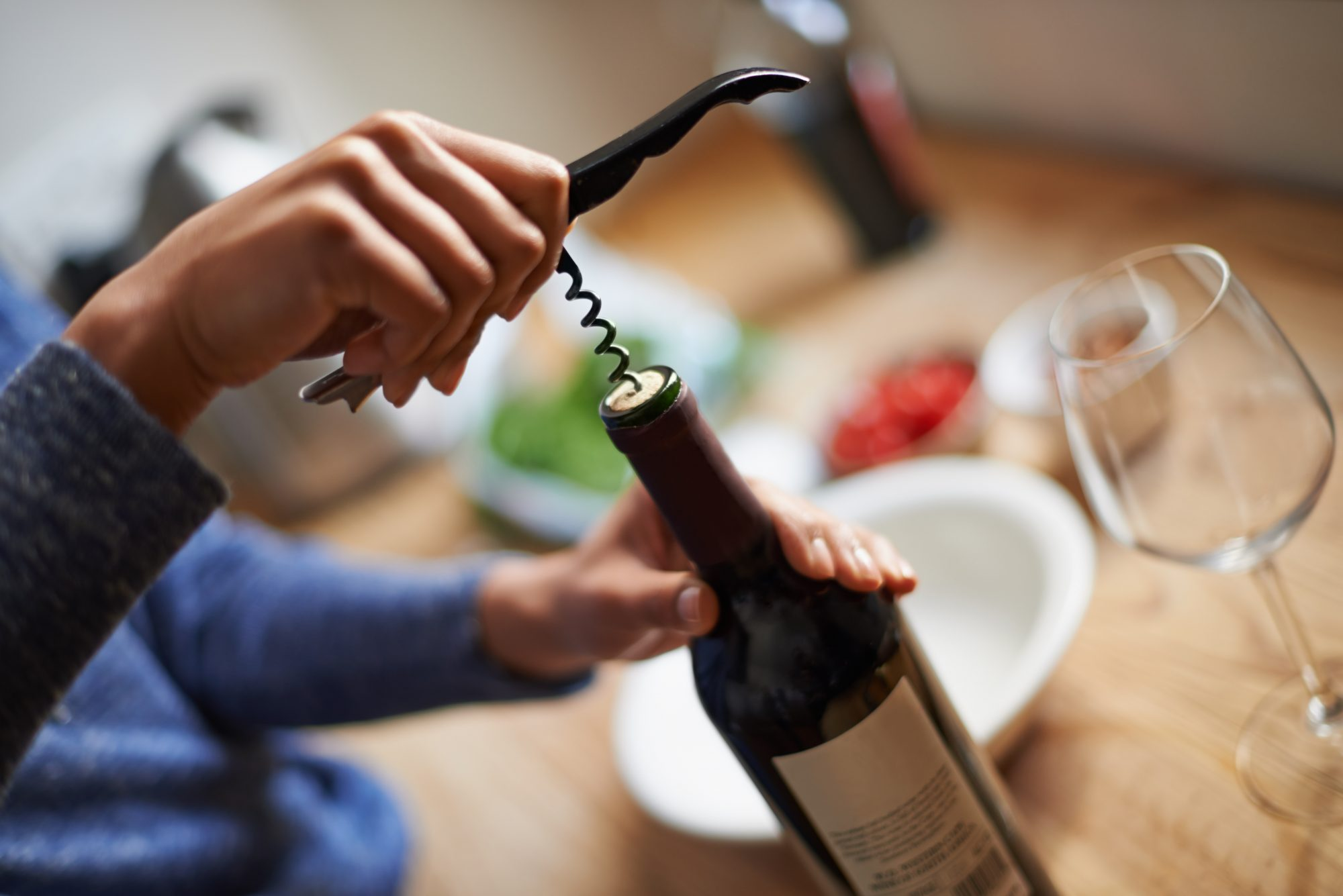 opening a wine bottle using a corkscrew